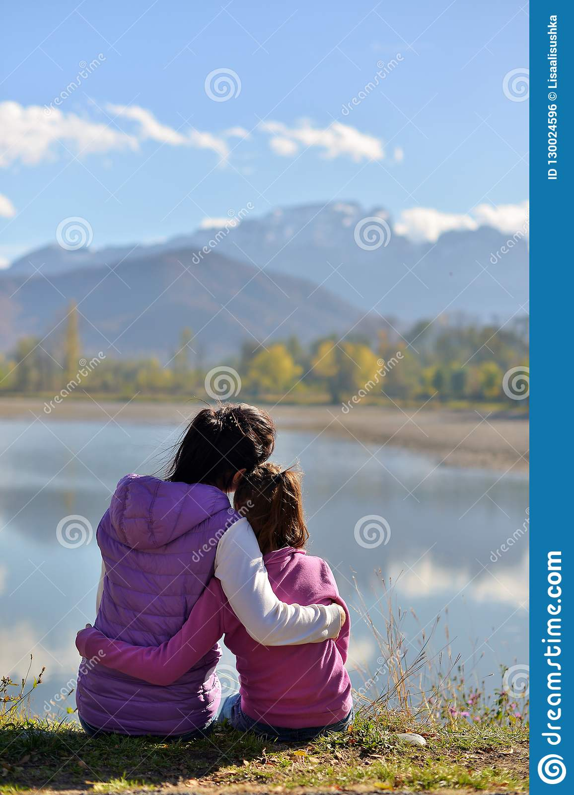 Mom and daughter sitting near the lake on the background of mountains.