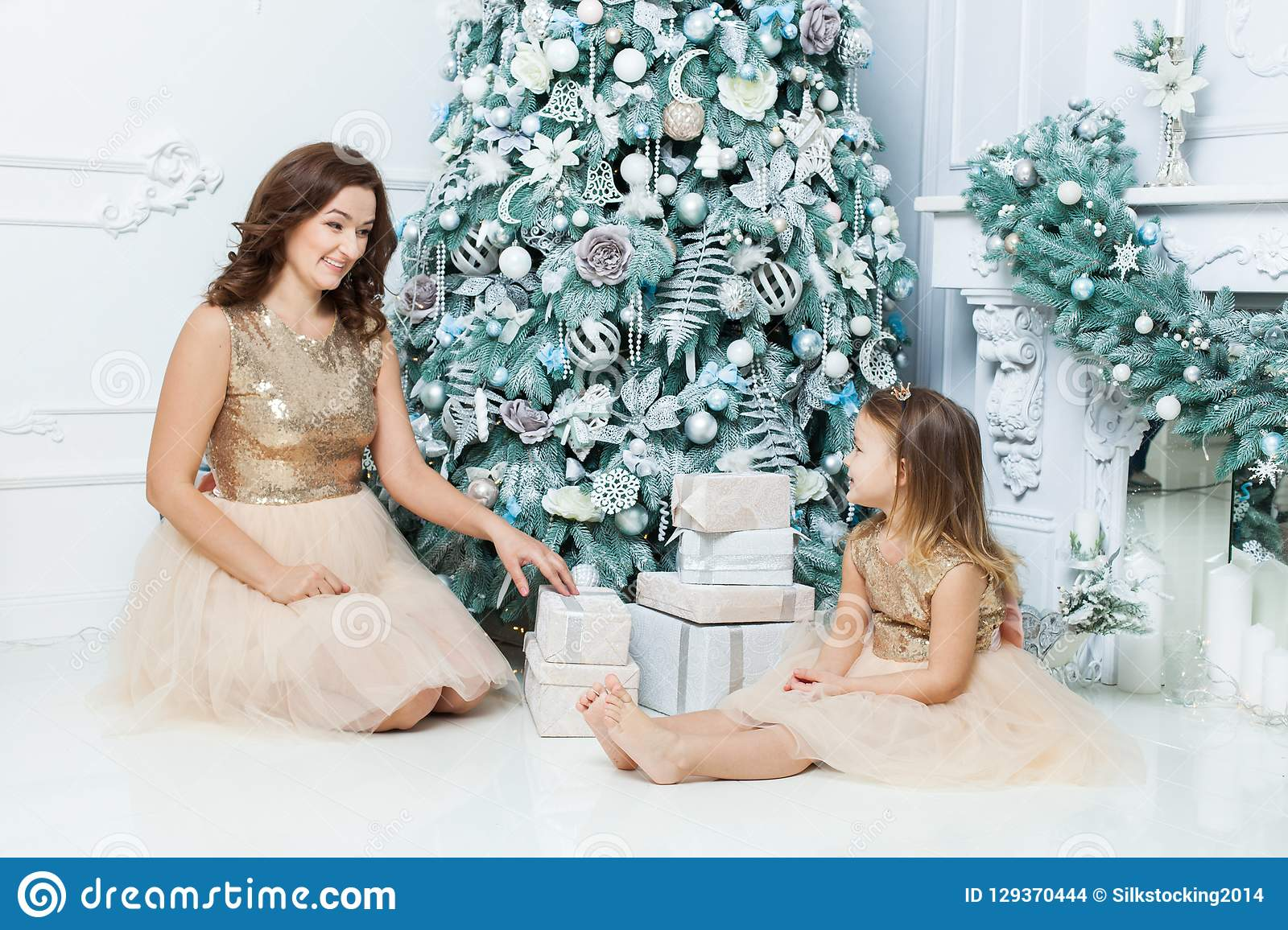 Mom And Daughter Sitting Under The Christmas Tree. Stock Photo ...