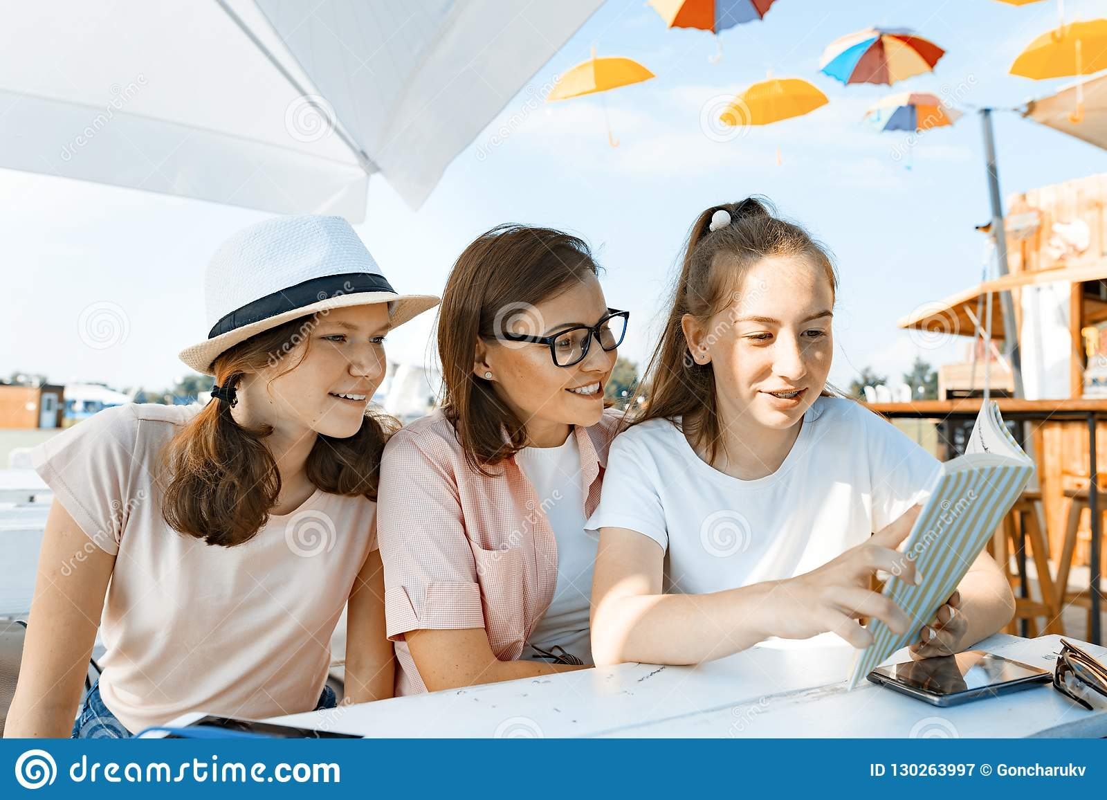 Mom and daughters teenagers have fun, talking, look and read funny book. Communication of the parent and children of adolescents.