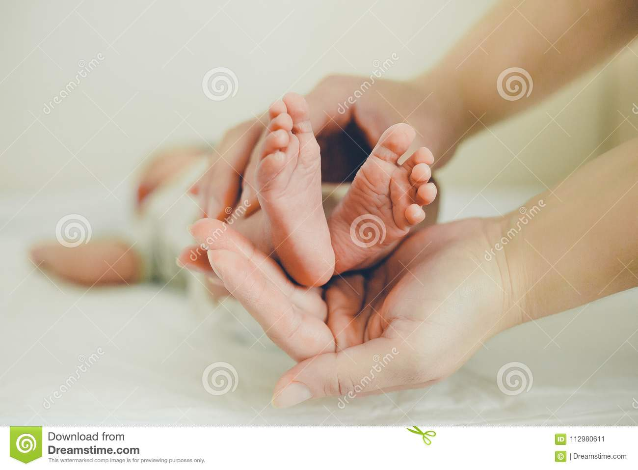 Mom gently massaging the tiny feet of a baby
