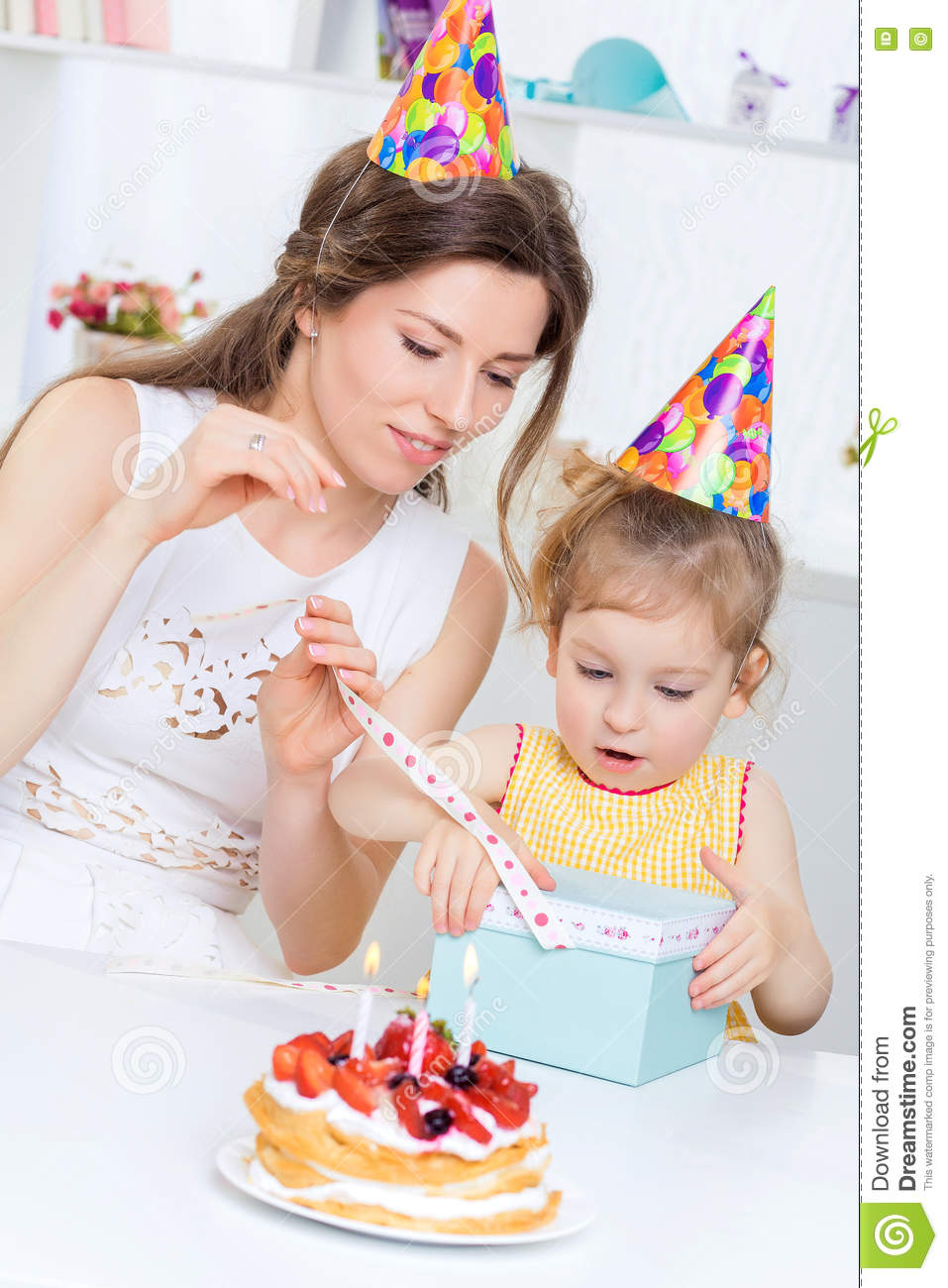 Young Beautiful Mother And Her Little Daughter Are Celebrating A Birthday On The Table Is Cake With Candles Happy Baby Mom Gives Gift