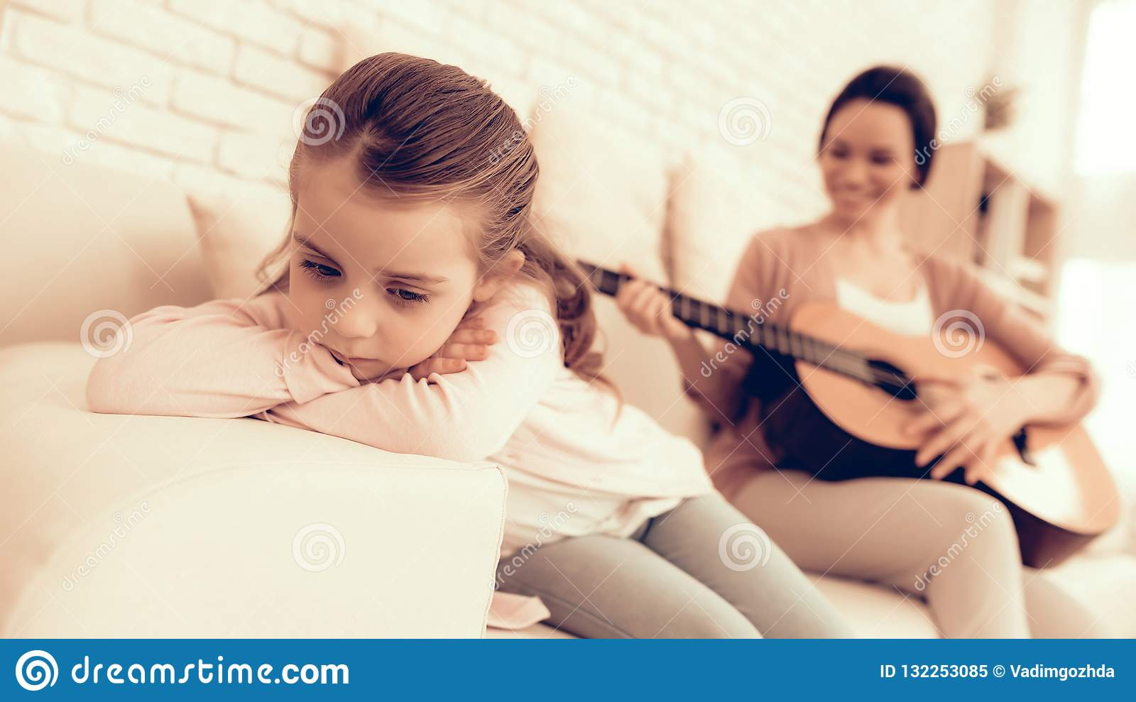Mom with guitar in hand and sad girl lie on sofa