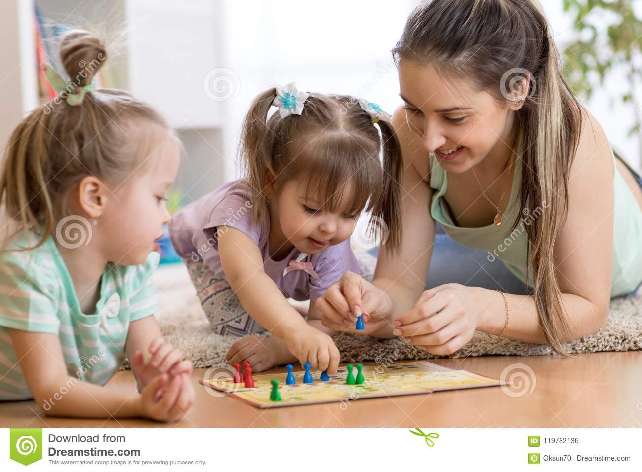 Mother And Her Kids Playing In Board Game Stock Photo