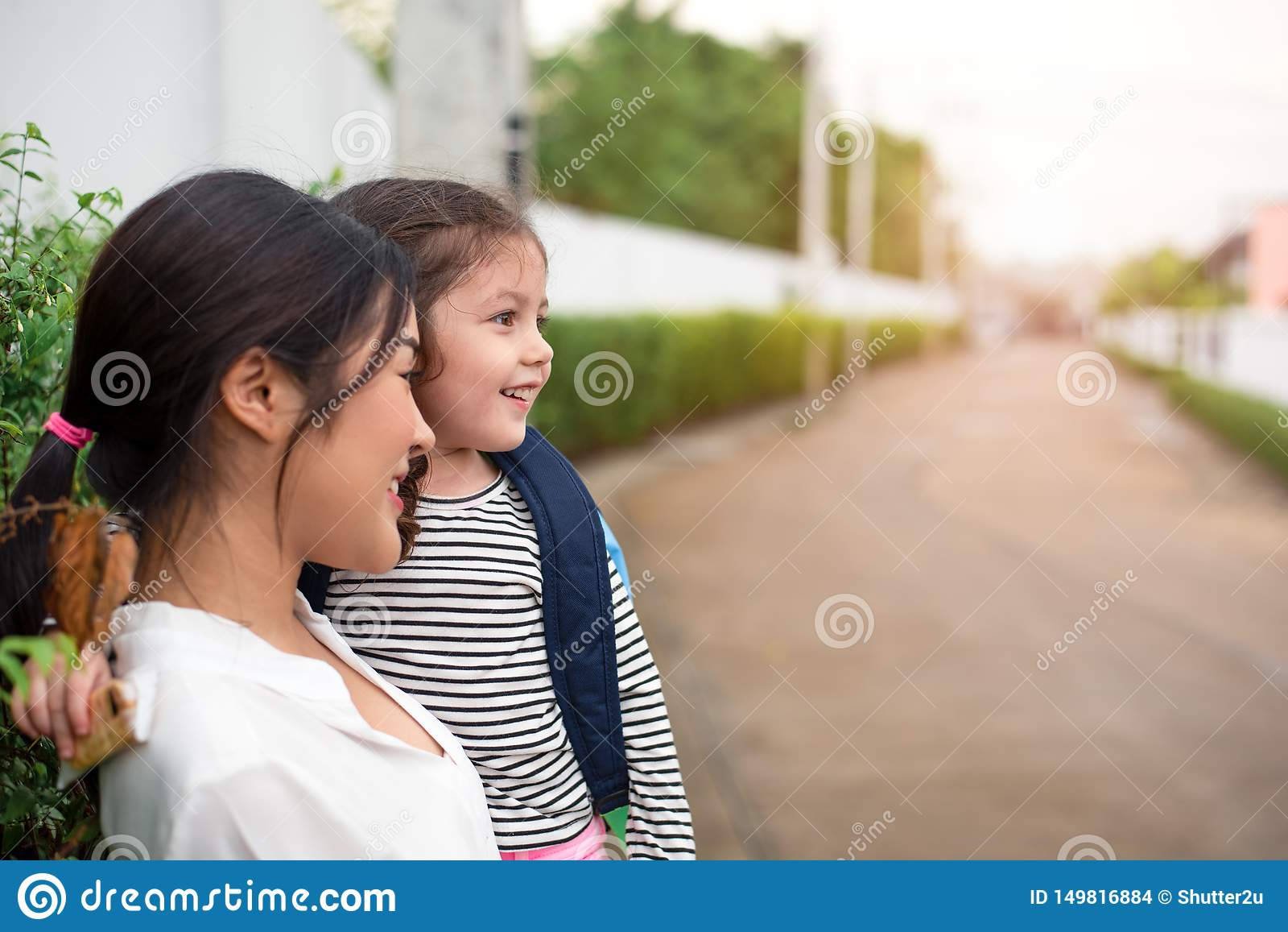 Mom and her daughter smiling together after going home from school. Love and daycare concept. Happy family and Home sweet home
