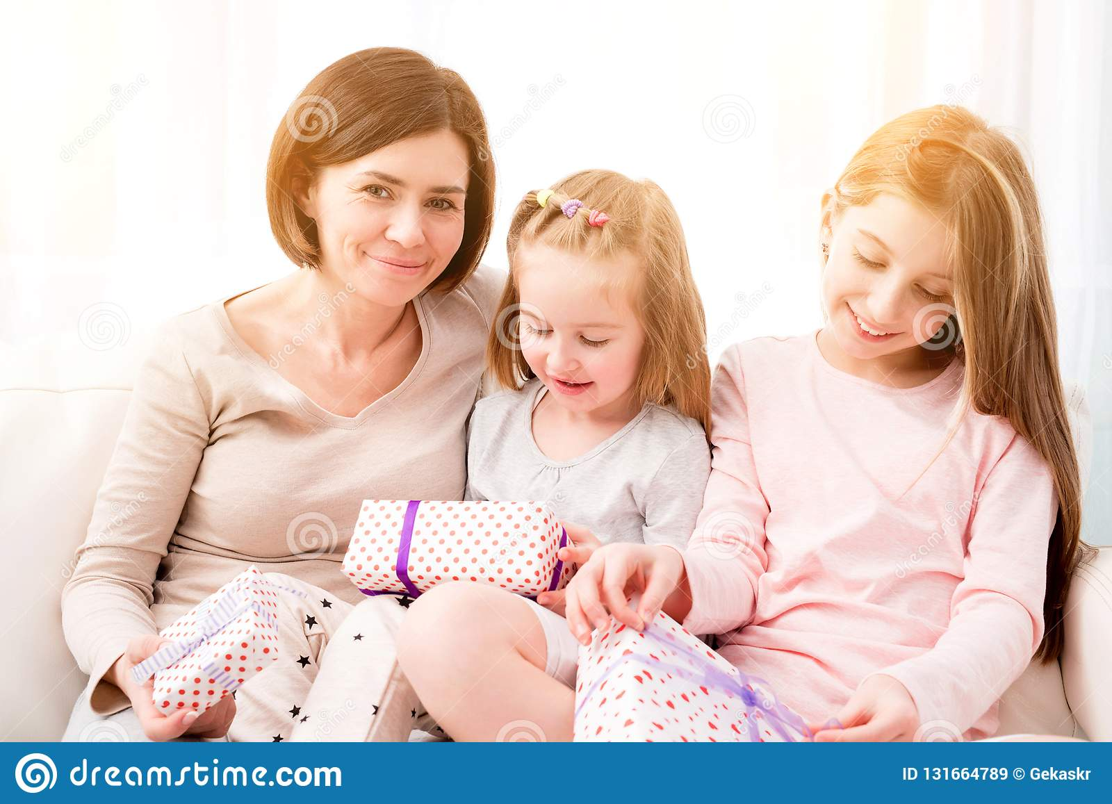 Cheerful Mom And Her Beautiful Daughters Exchanging Gifts Happy Birthday Womans Day Mothers Christmas
