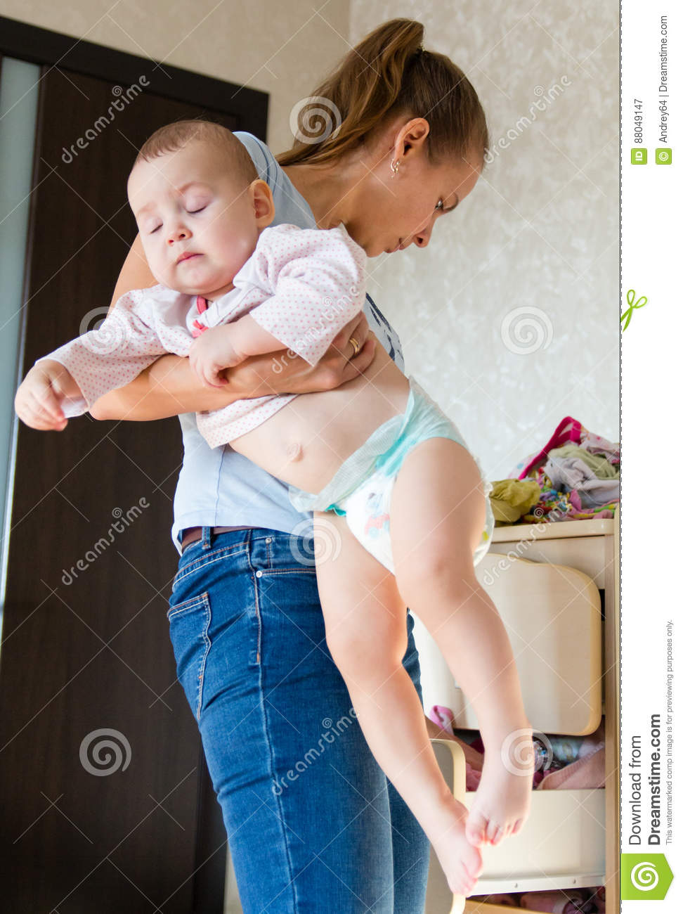 Mom holding baby. Mom cleans baby clothes