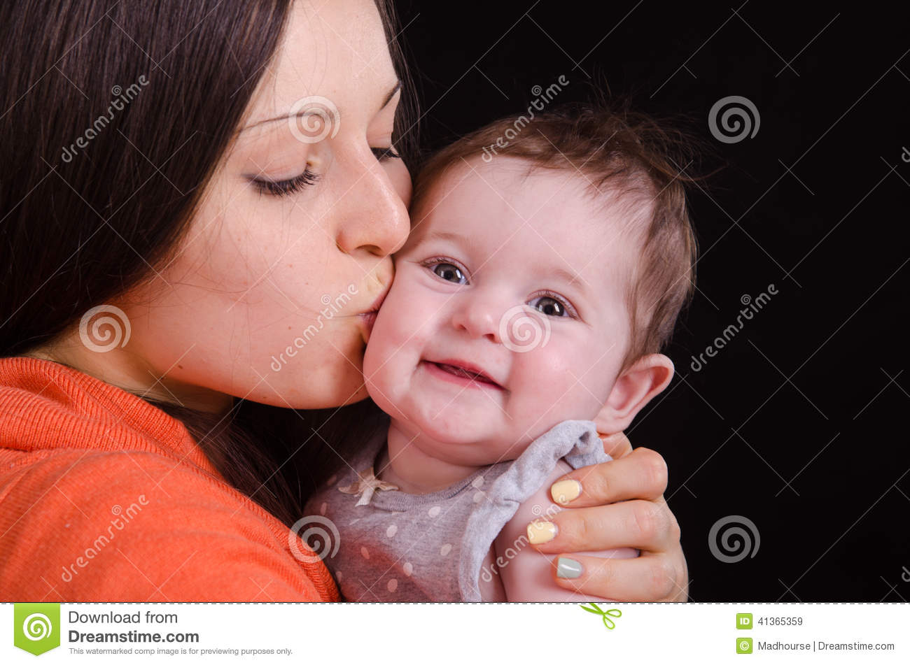 Mom kisses the baby of six months