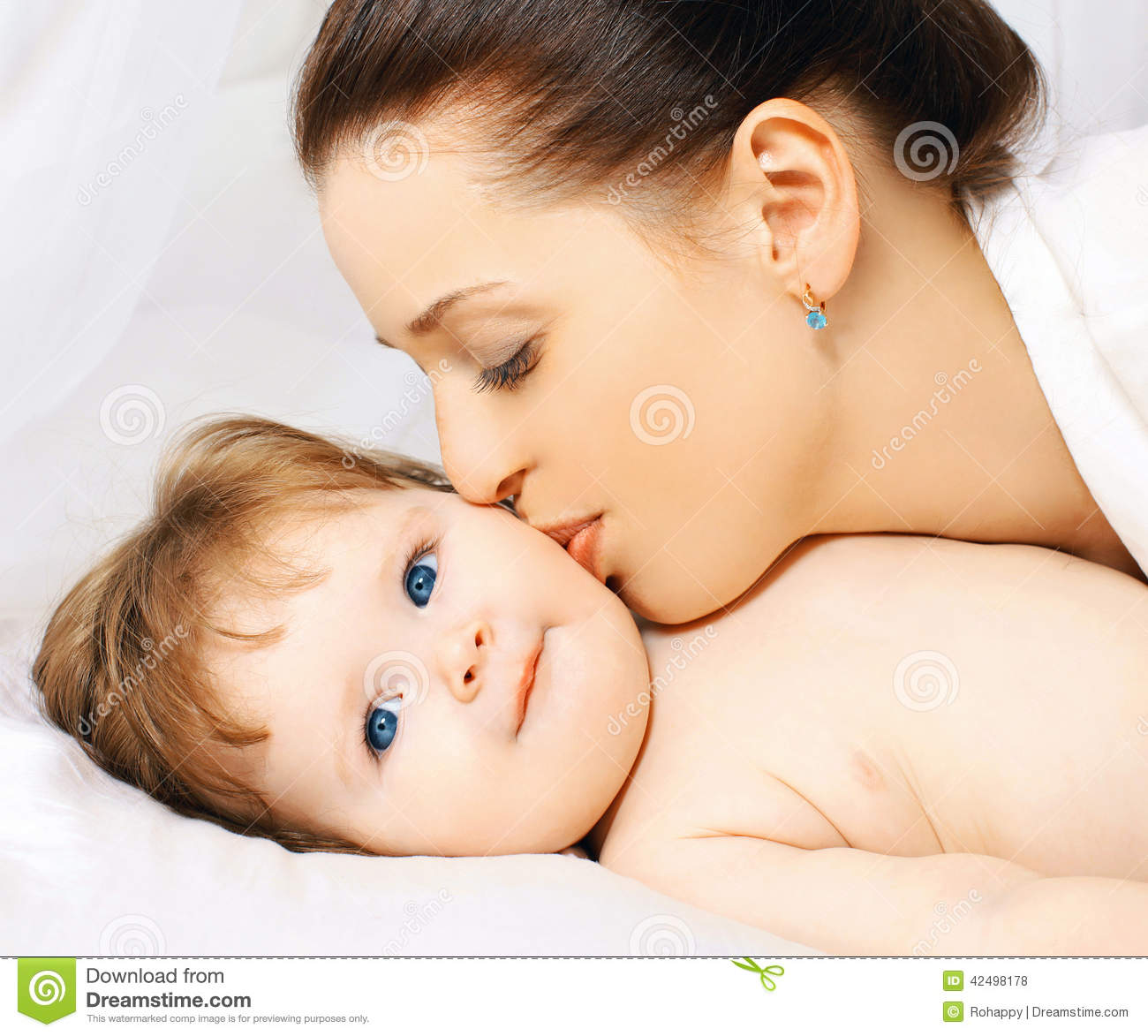Baby bed next to mom - Mom Kissing Baby In Bed Royalty Free Stock Photos