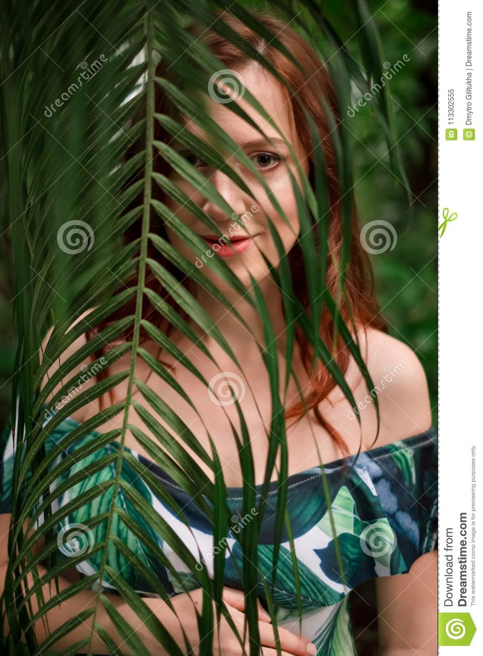 f3945e72fc963 Royalty-Free Stock Photo. Beautiful young pregnant caucasian redhead woman  in palm leaves