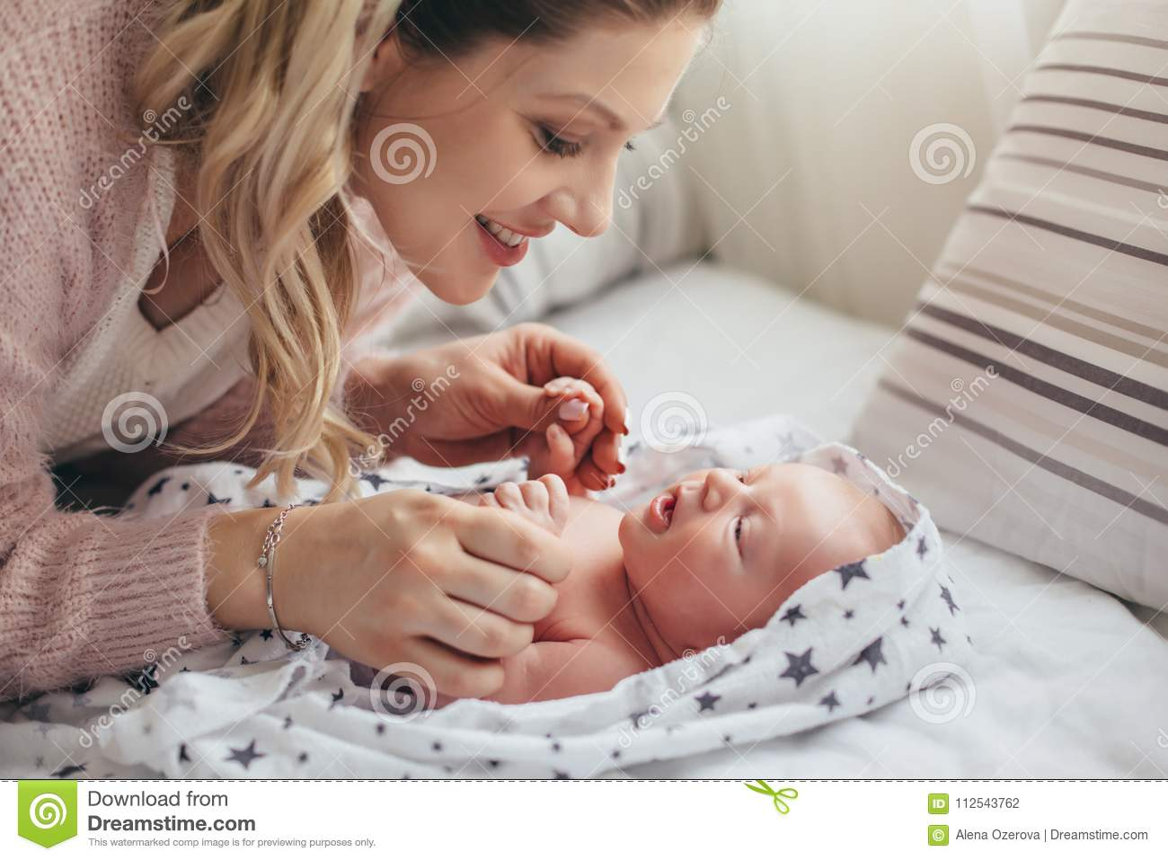 Home portrait of a newborn baby with mother on the bed moms care for the child
