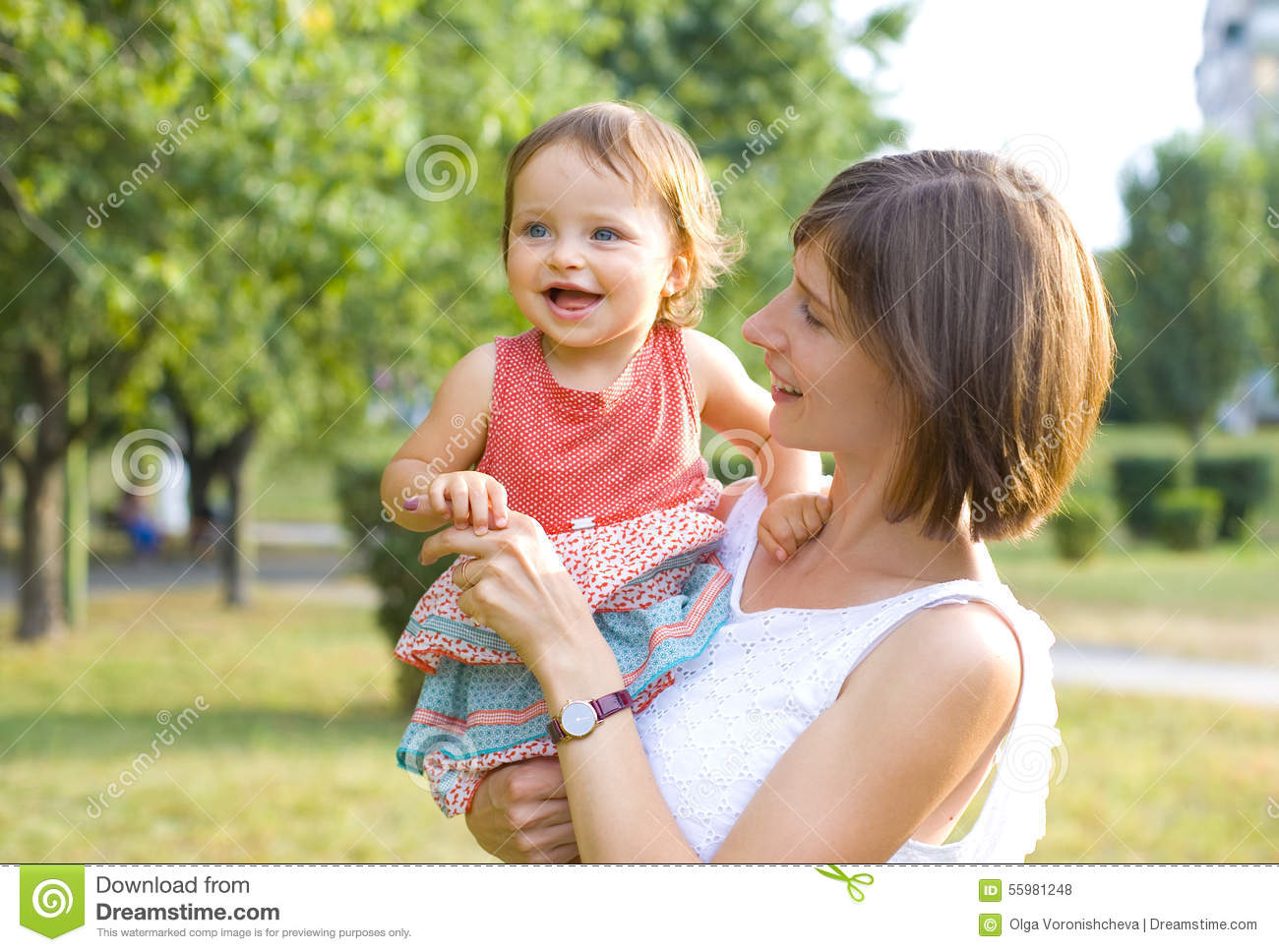 Attractive young mother holding a little girl in her arms