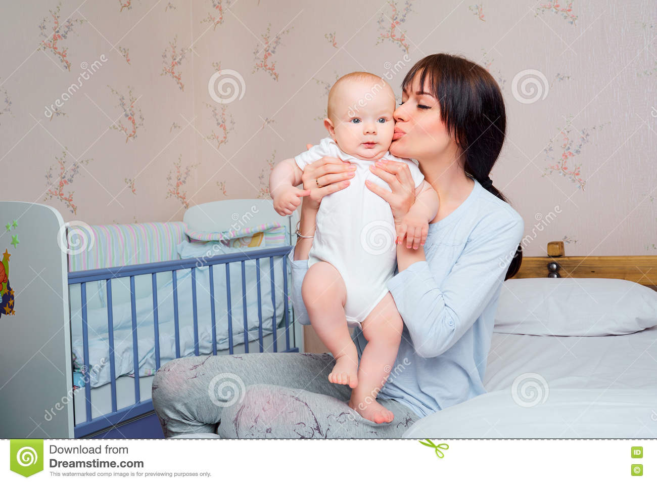 Baby bed next to mom - Mom Pajamas Tenderly Kisses The Baby Boy On The Bed In The Room