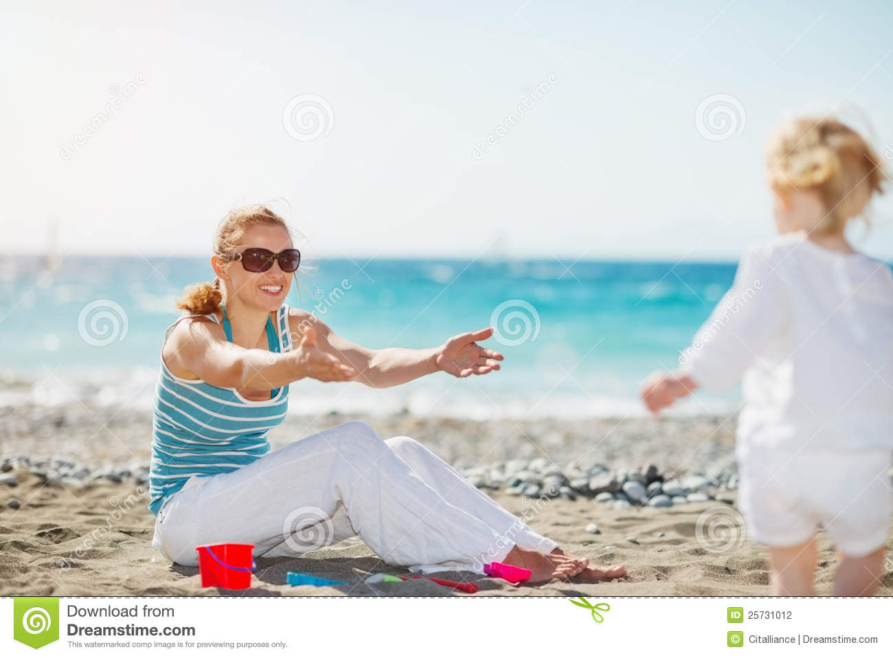 Mom playing with baby on beach