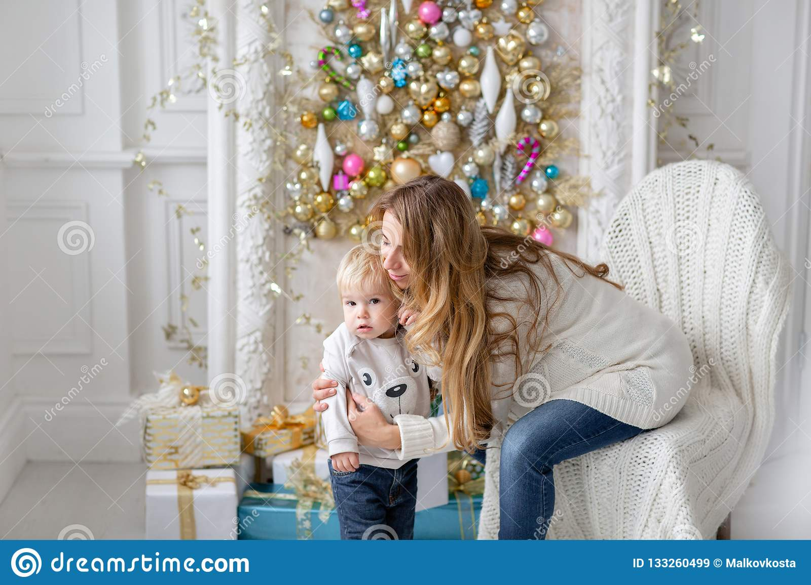 Mom plays with child. Happy family Portrait In Home - young pregnant mother embraces his little son. Happy new year