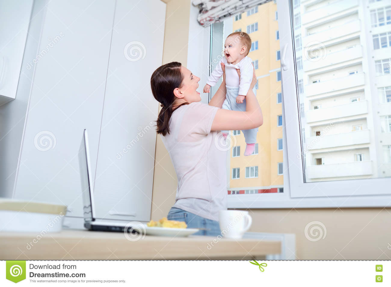 Mom Plays With The Child At The Window In The White Kitchen Stock ...