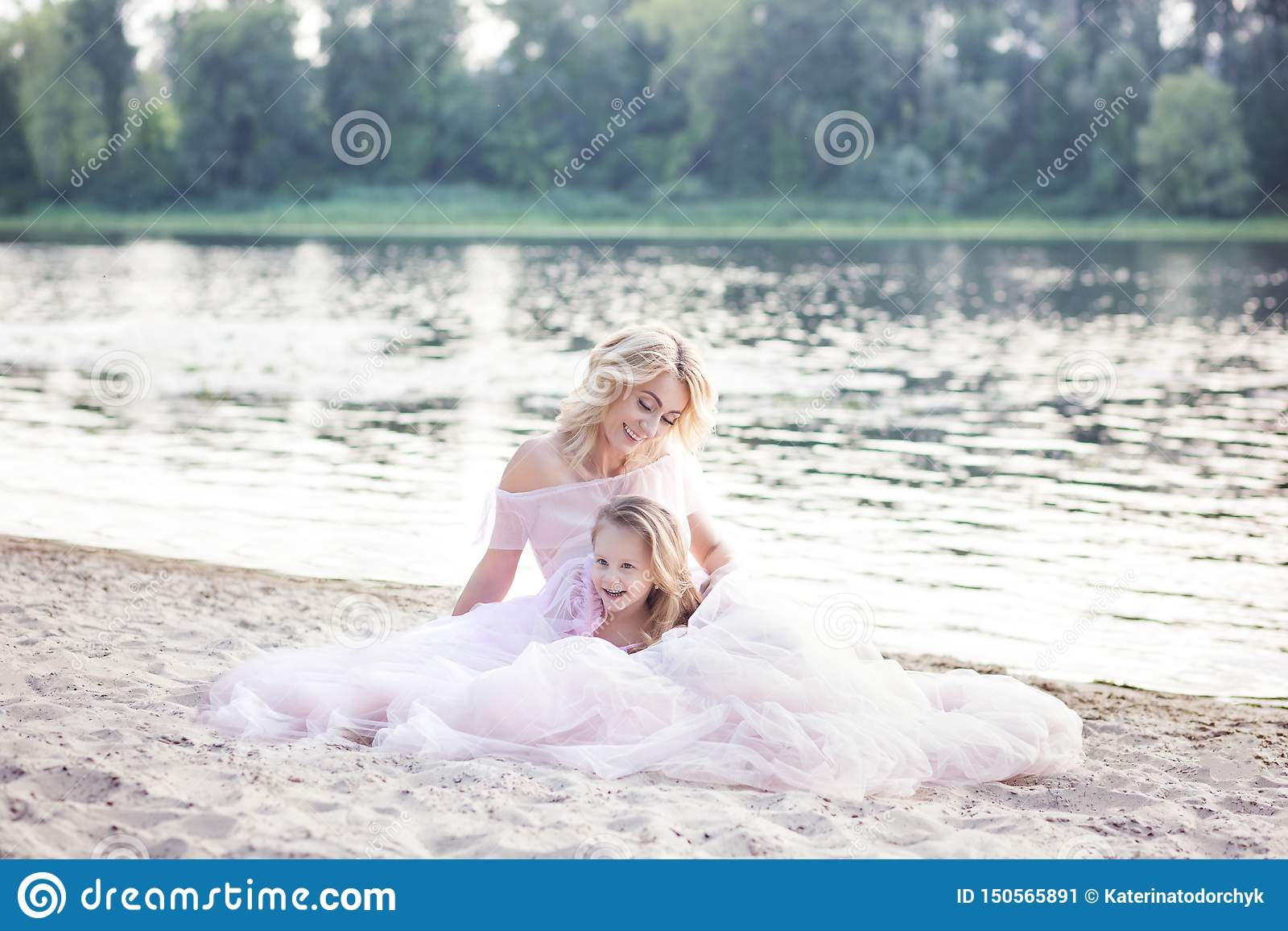 Mom plays with her child on a vacation by the lake. Family lifestyle and love concept. Mother and daughter having tender moments o