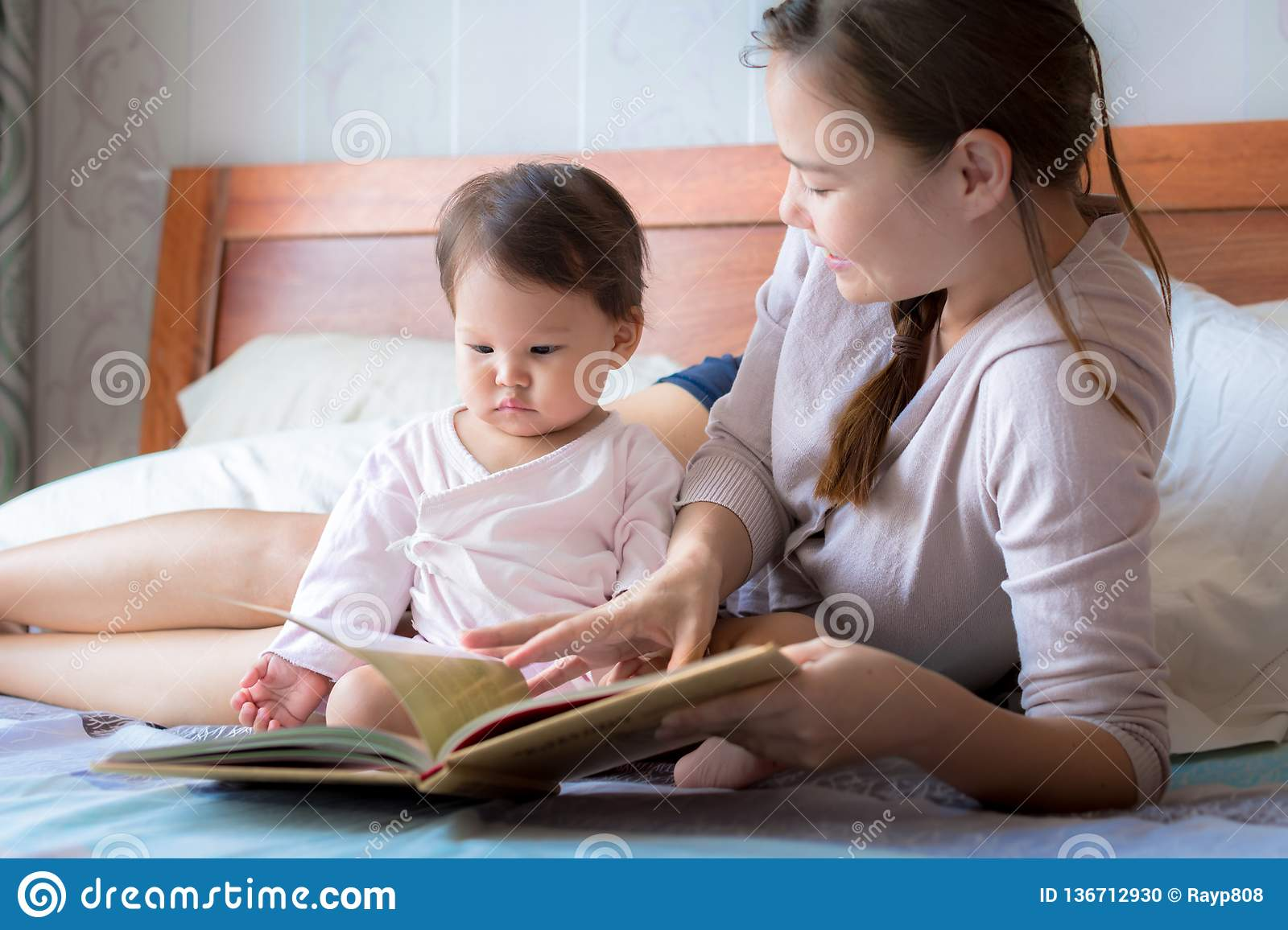 Mother reading a book to her child on the bed. Bedtime story. Learning how to read