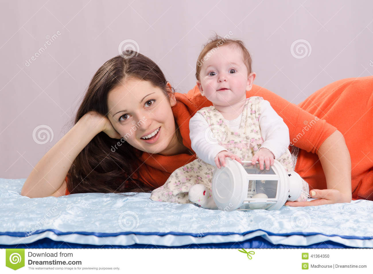 Mom with a six-month daughter playing on the bed