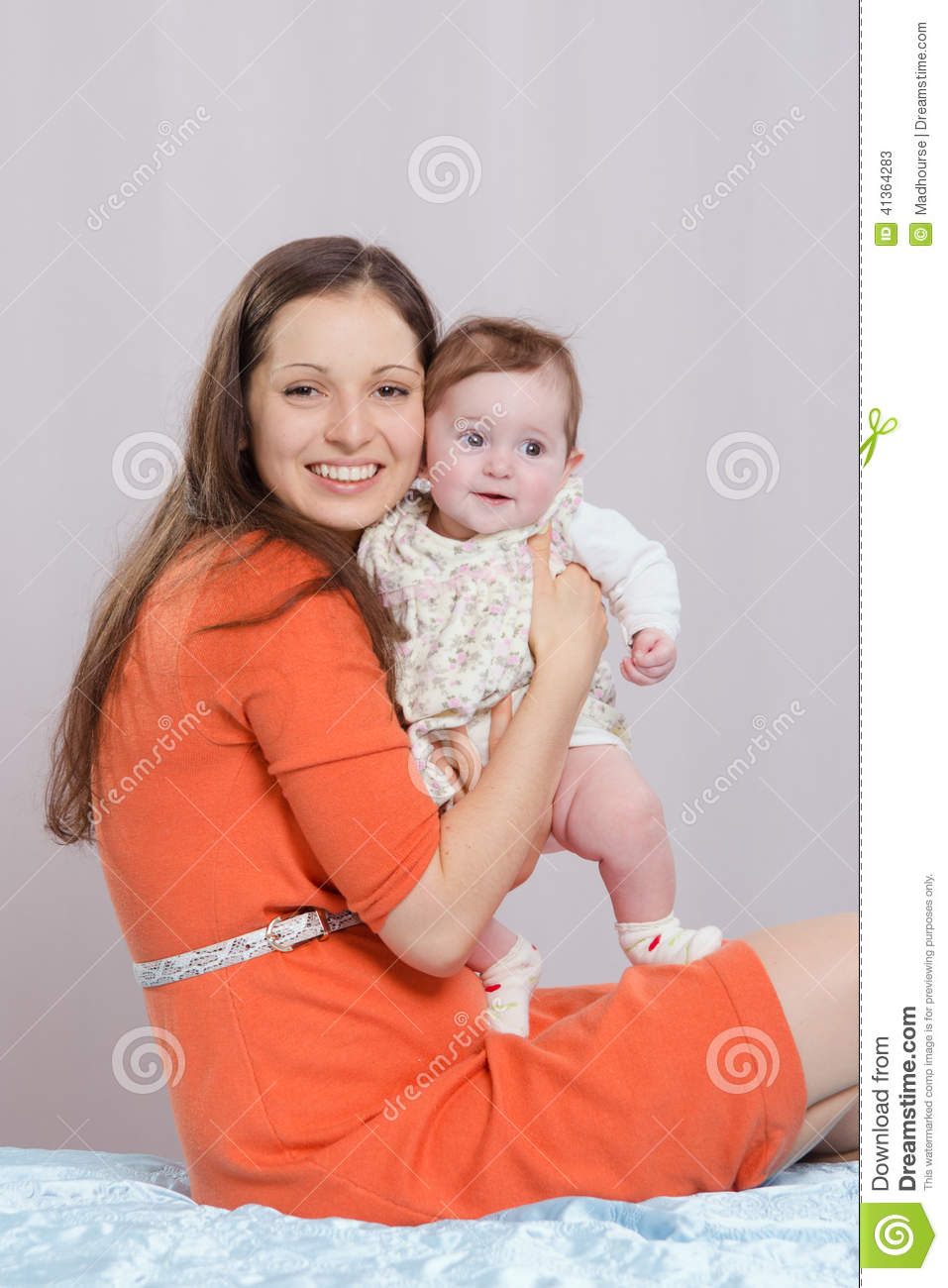 Mom with a six-month daughter sitting on bed