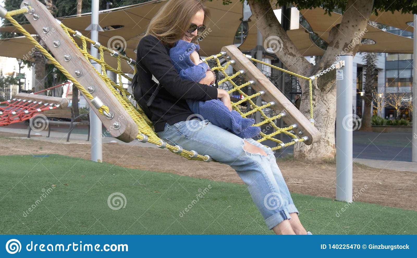 Mom and small funny baby have fun shakeing in hammock