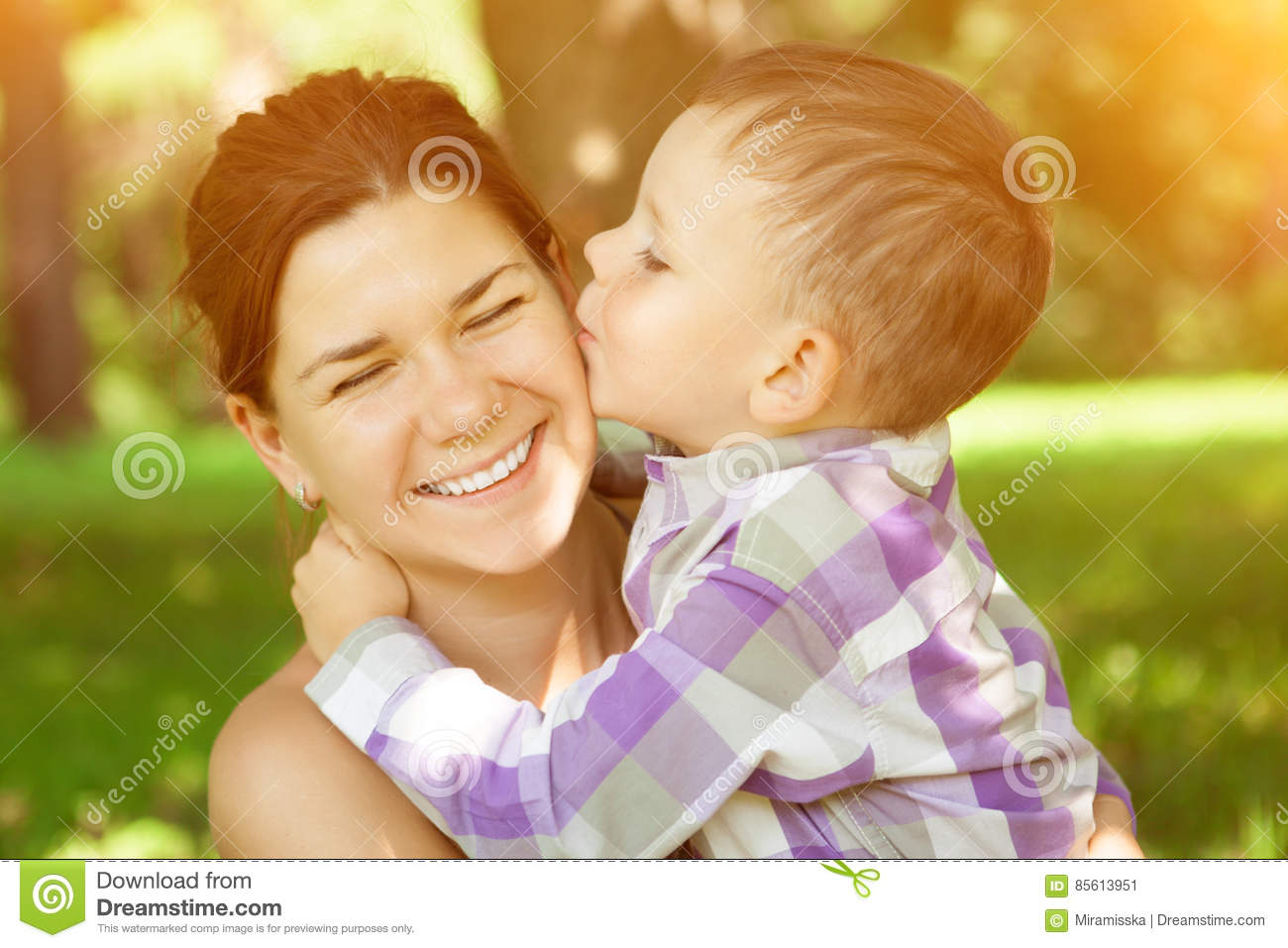 Mom And Son Child Kisses His Mother On Nature Background Posit