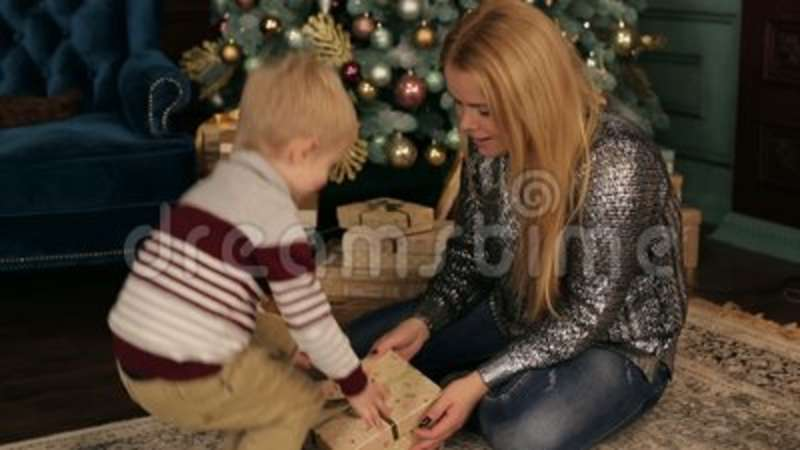 Mom And Son Open Christmas Gifts Near The Tree. Stock Footage ...