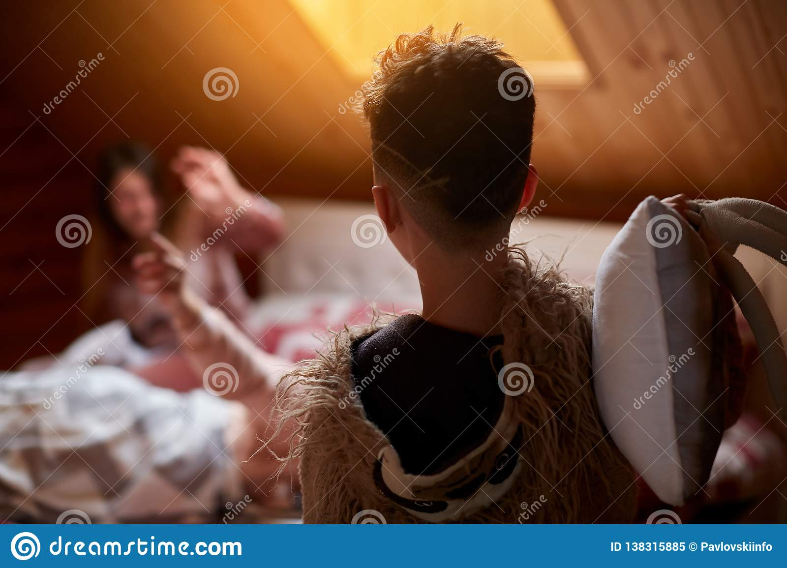 Mom and son play on the bed, in the morning arrange a pillow fight in their pajamas