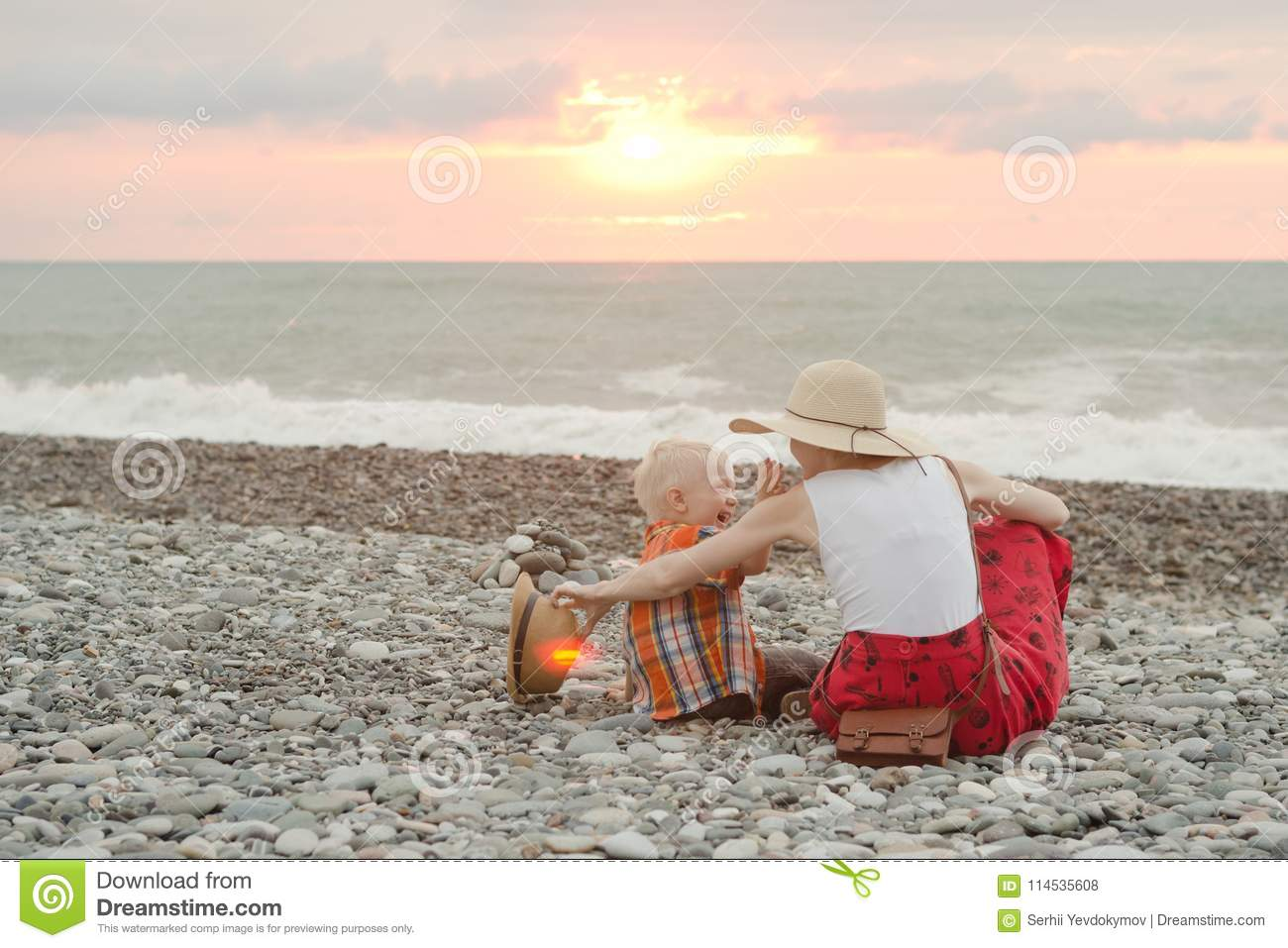 Mom and son play on the pebble beach. Sunset time. Back view