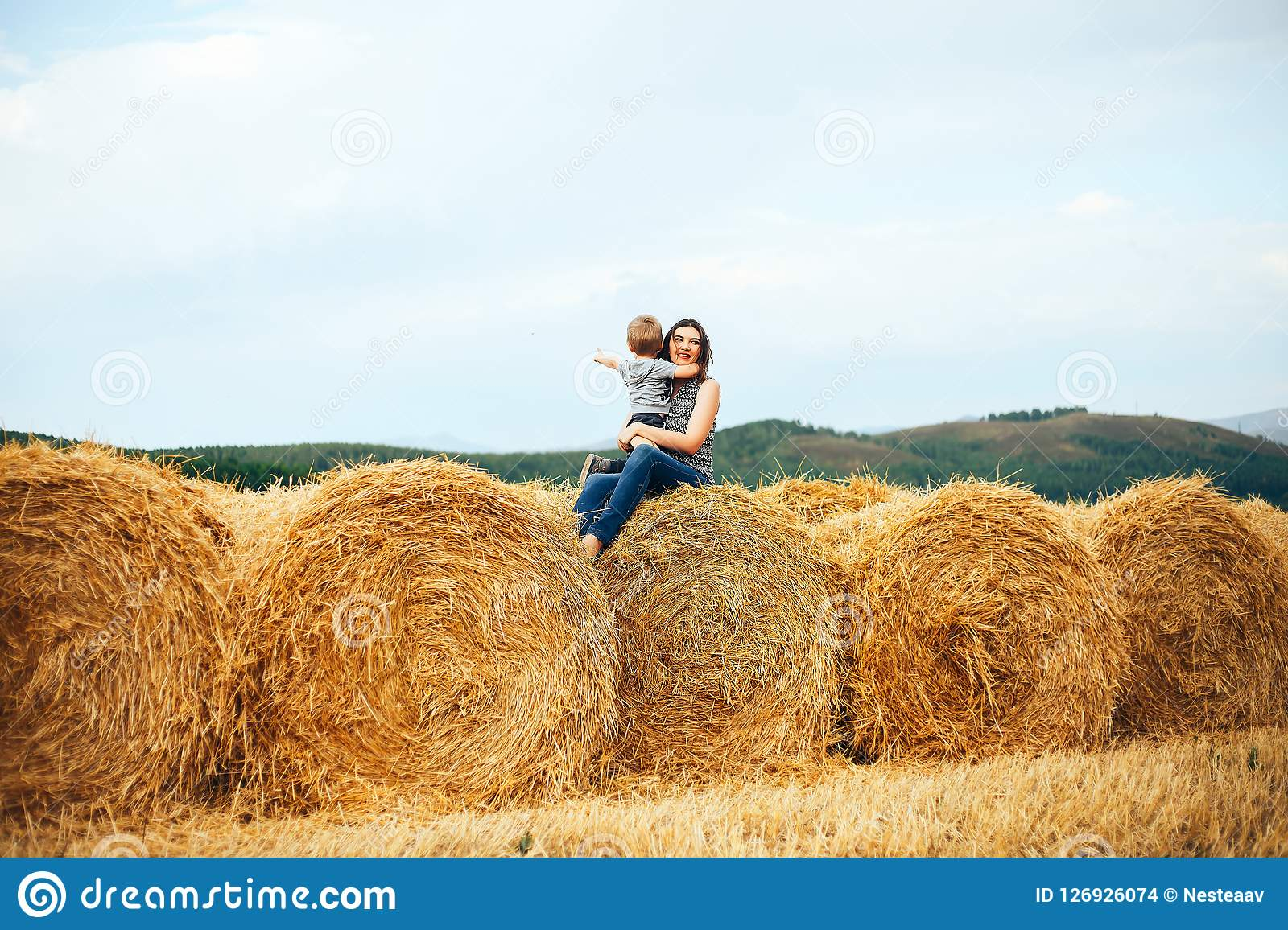 Happy mother with son in summer at field and straw haystack