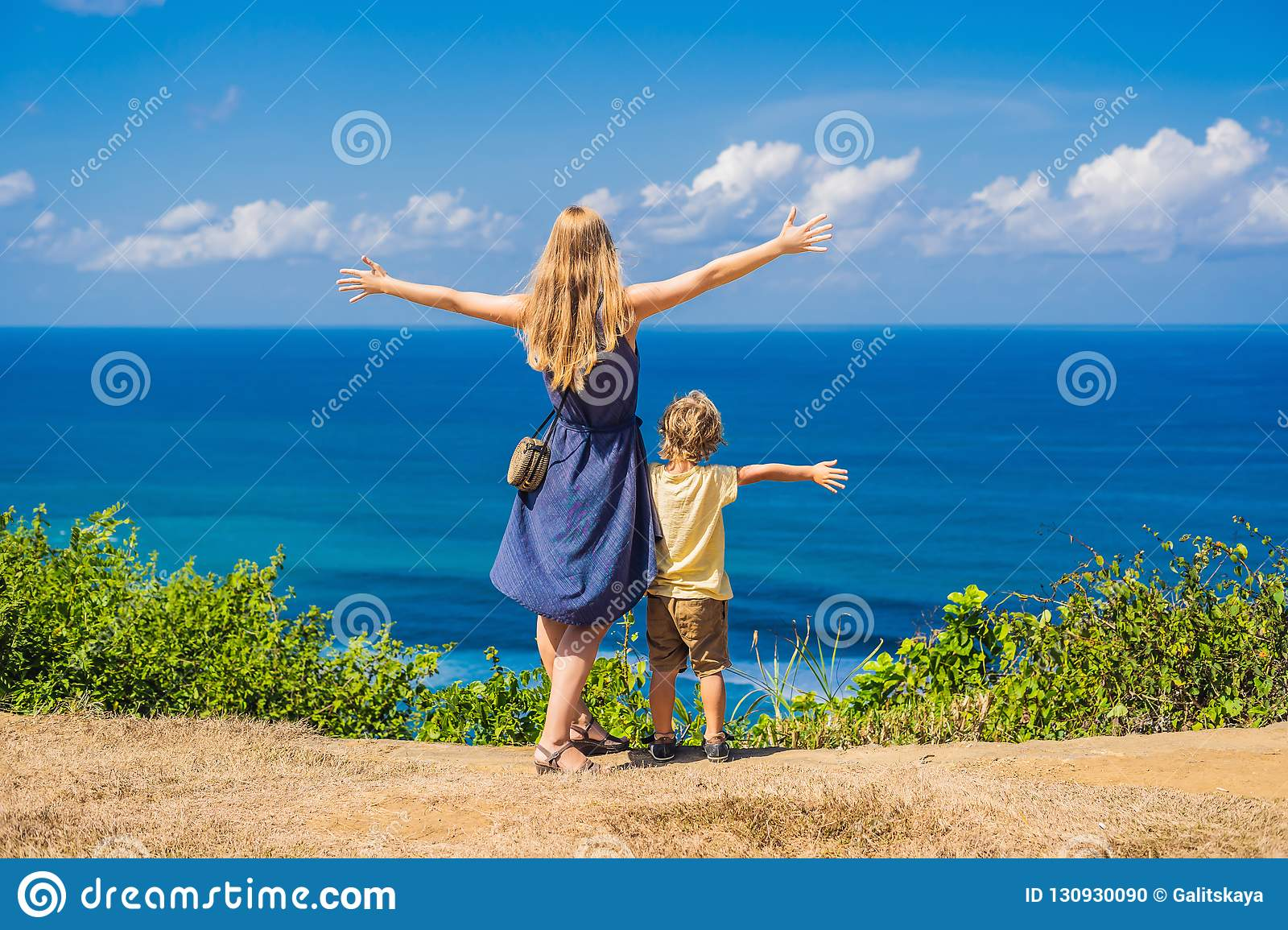 Mom and son travelers on a cliff above the beach. Empty paradise