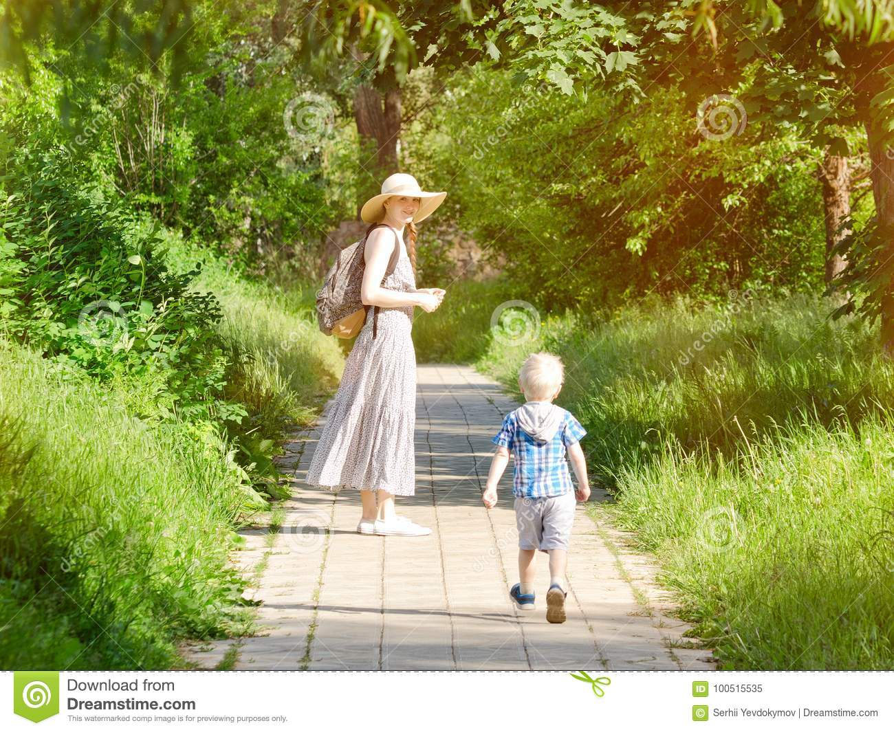 Mom and son walking along the road in the park. Back view. Vertical frame