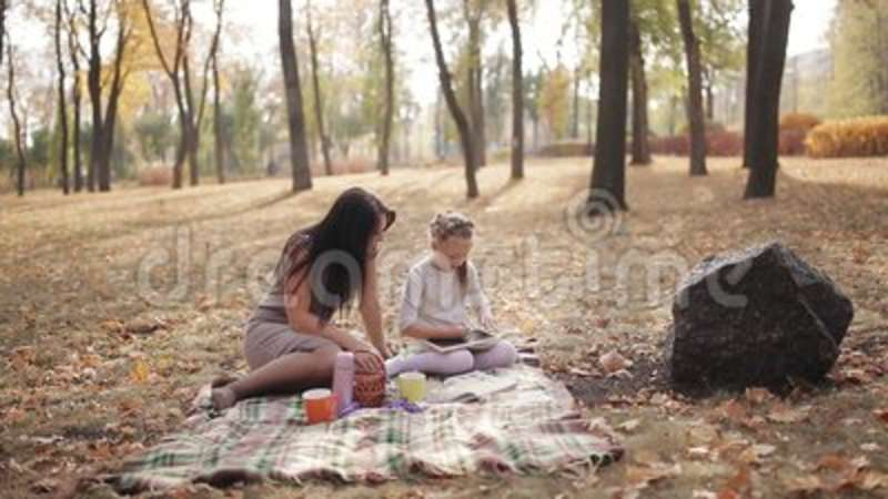Mom teaches her daughter to write with chalk on a blackboard letters, the  alphabet  Happy family outdoors  Mother and