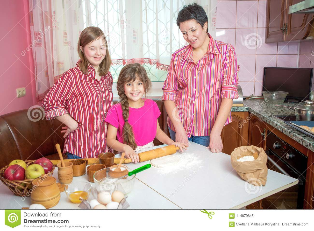 Mom Teaching Her Two Daughters Cooking On The Kitchen  Stock