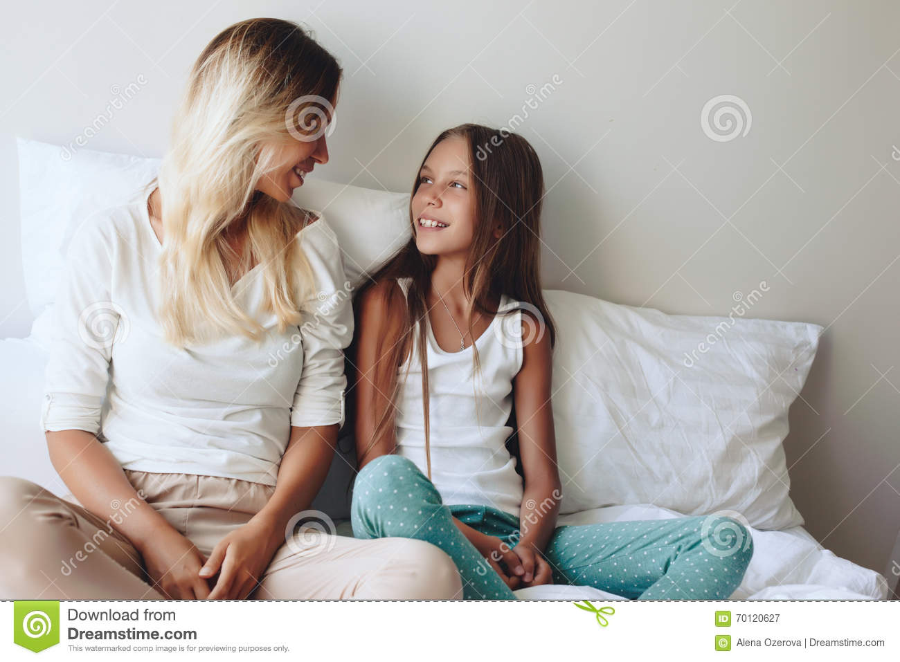Mom with her tween daughter relaxing in bed positive feelings good