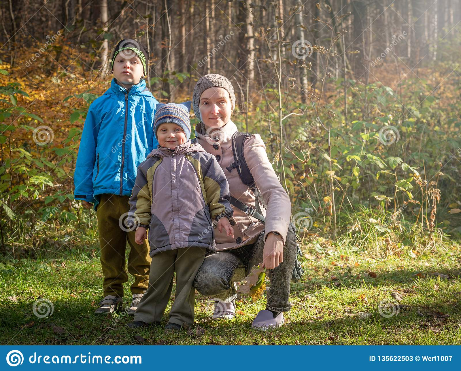 Mom with two children walking in the autumn forest