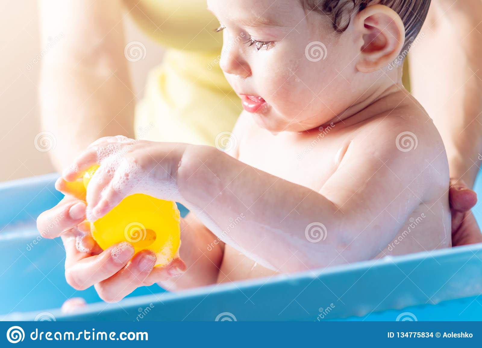 Mom washing little boy in a blue bath. Child is bathing with a yellow duck. Hygiene and water treatment with the baby