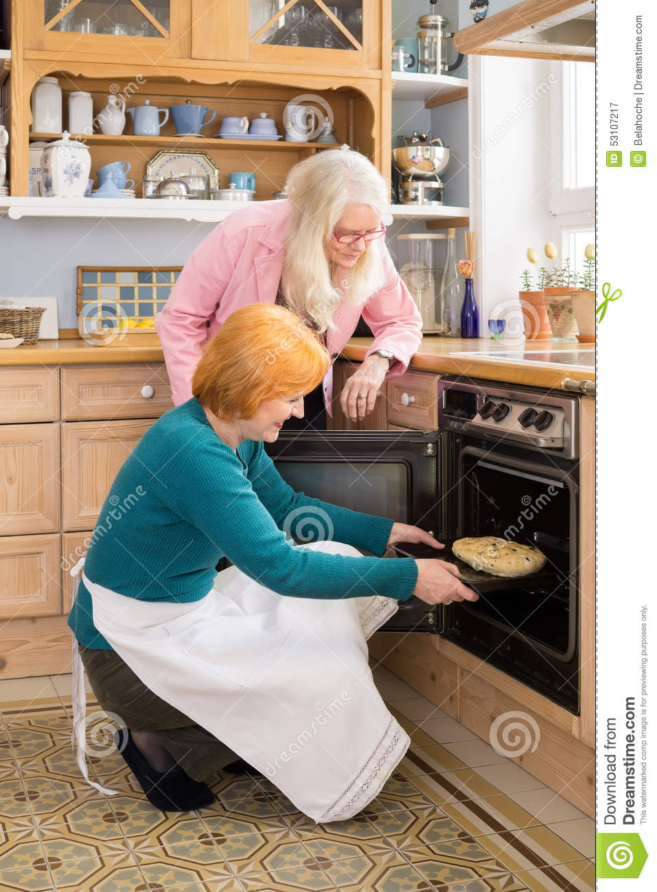 Watch Mom In Bedroom Camera: Mom Watching Other Mom Putting Cake In An Oven Stock Image