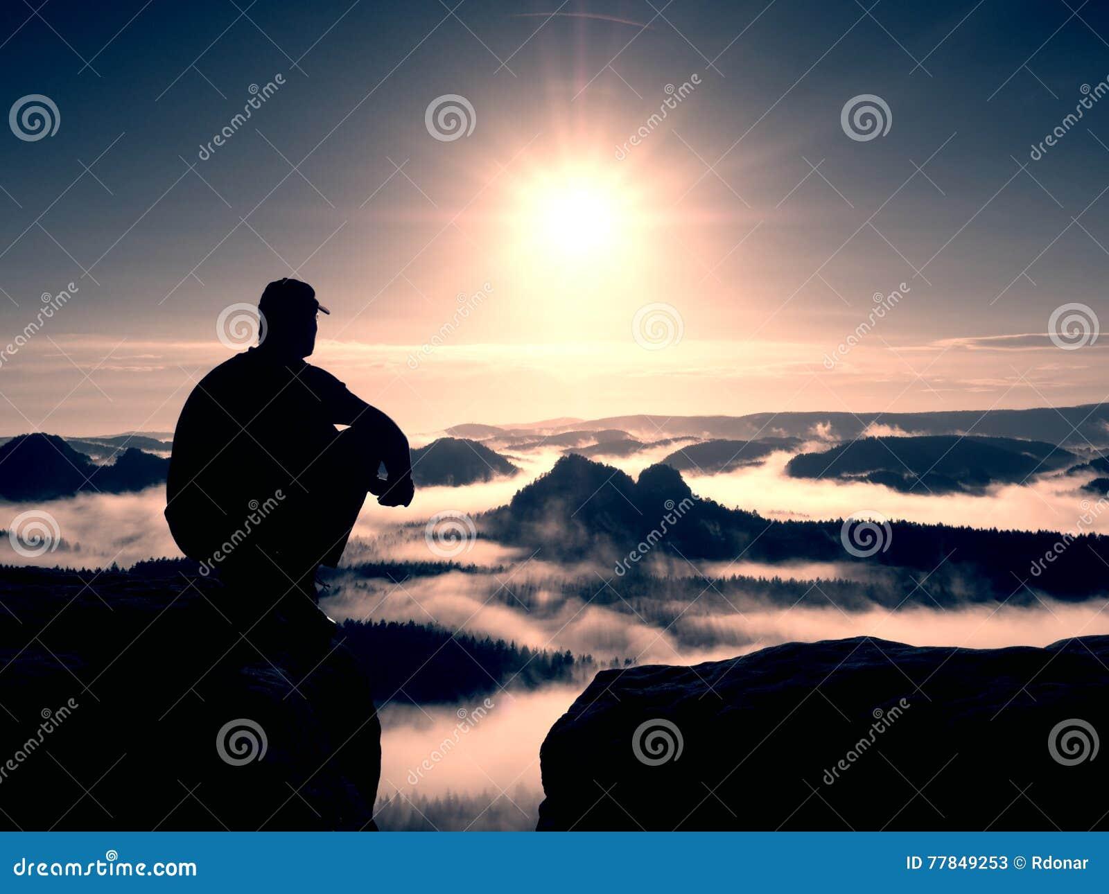 Moment de solitude L homme avec le chapeau s asseyent sur la montagne et la  montre c88cf58f654