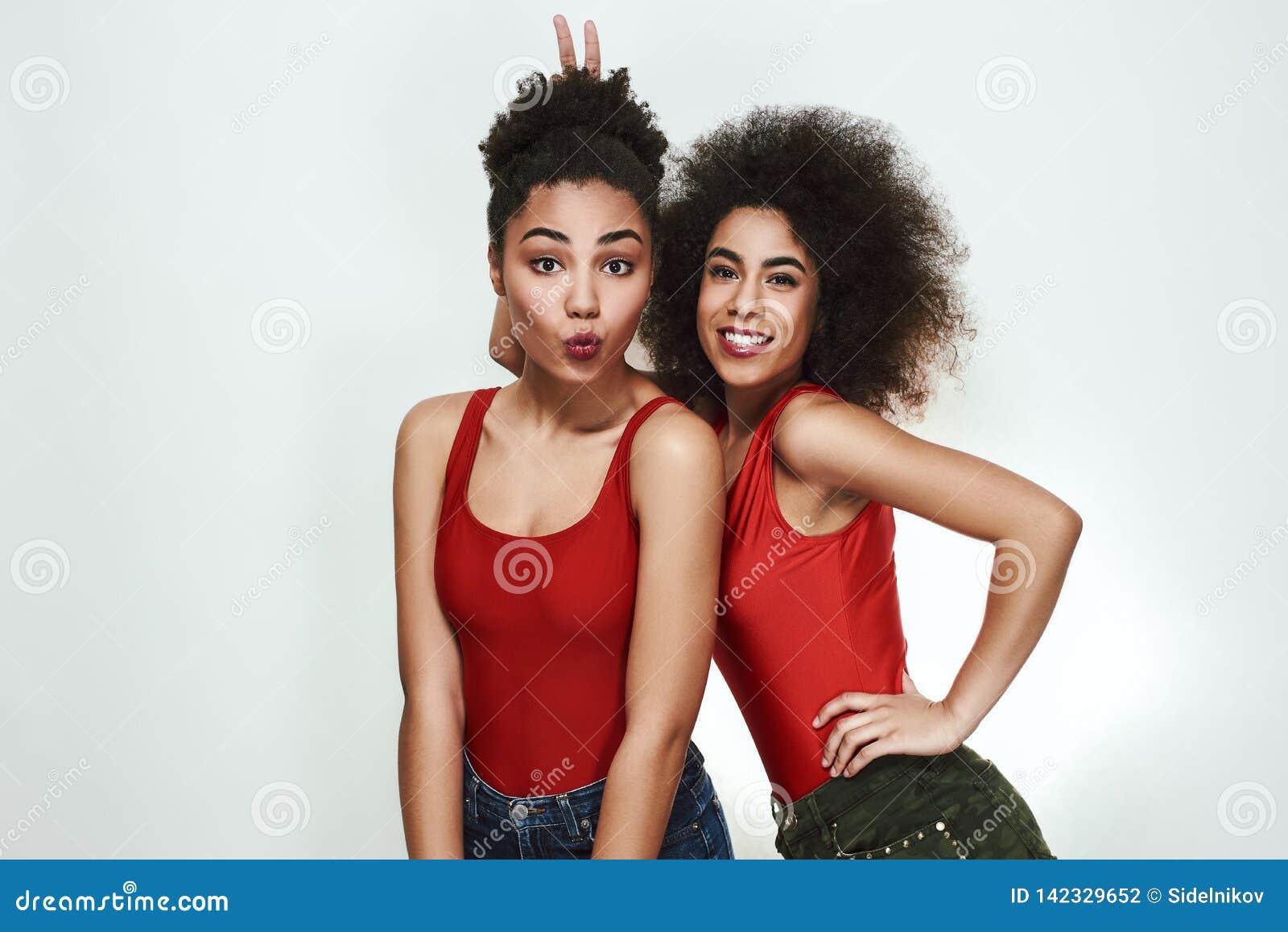 Momentos felizes Duas mulheres afro-americanas bonitos no short das calças de brim são gesticulando e de fatura uma cara ao estar