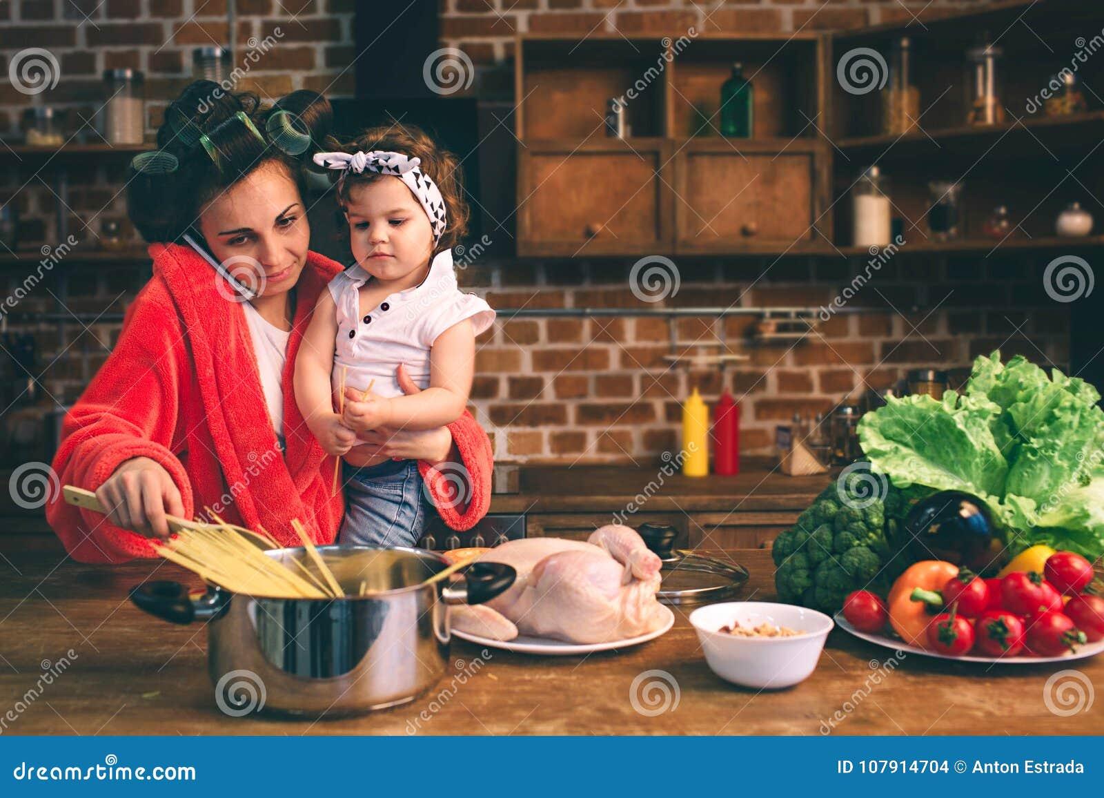 Momia subrayada en casa Madre joven con el pequeño niño en la cocina casera Mujer que hace muchas tareas mientras que se ocupa la