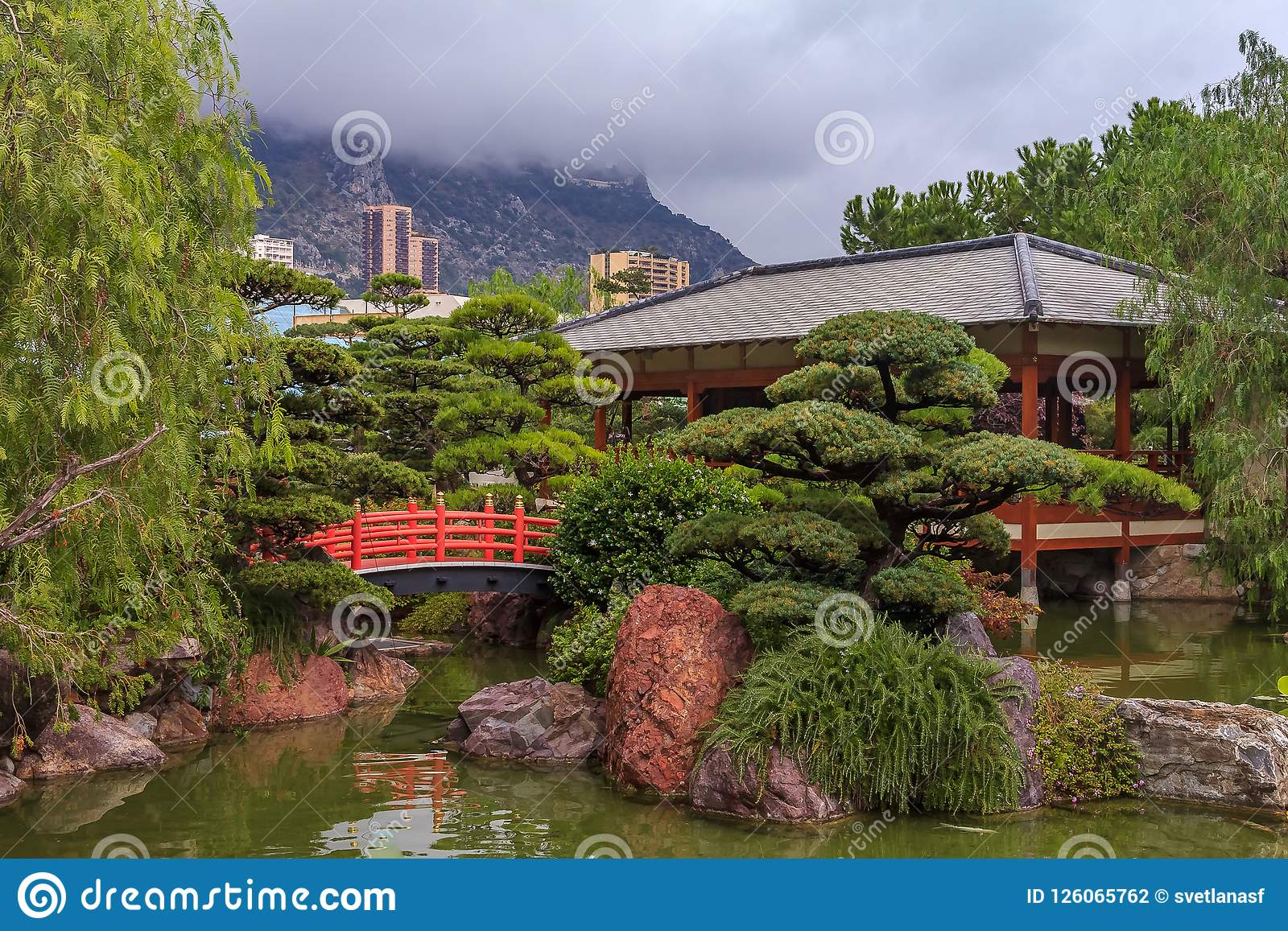 Japanese Garden Or Jardin Japonais With Residential Buildings In