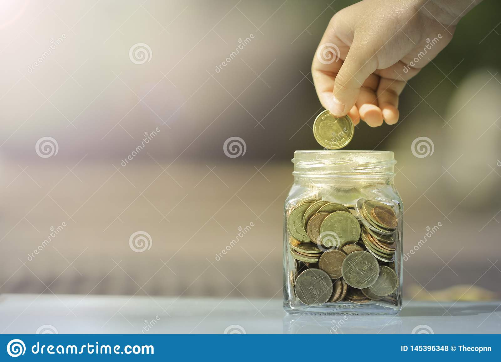 Moneda del ahorro del niño en la hucha de cristal