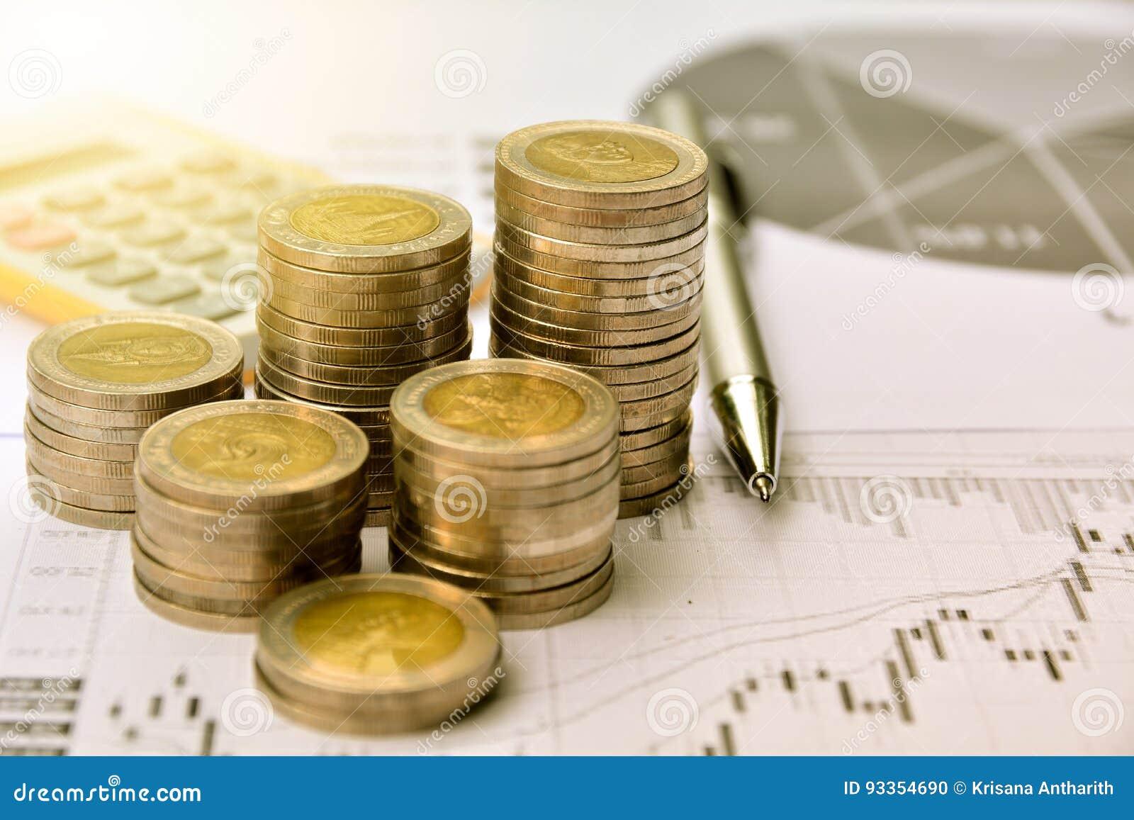Monedas del dinero con el papel cuadriculado y calculadora, finanzas y crecimiento