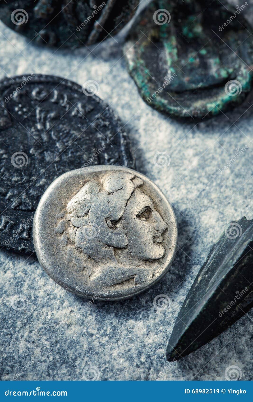 Monedas y punta de flecha romanas