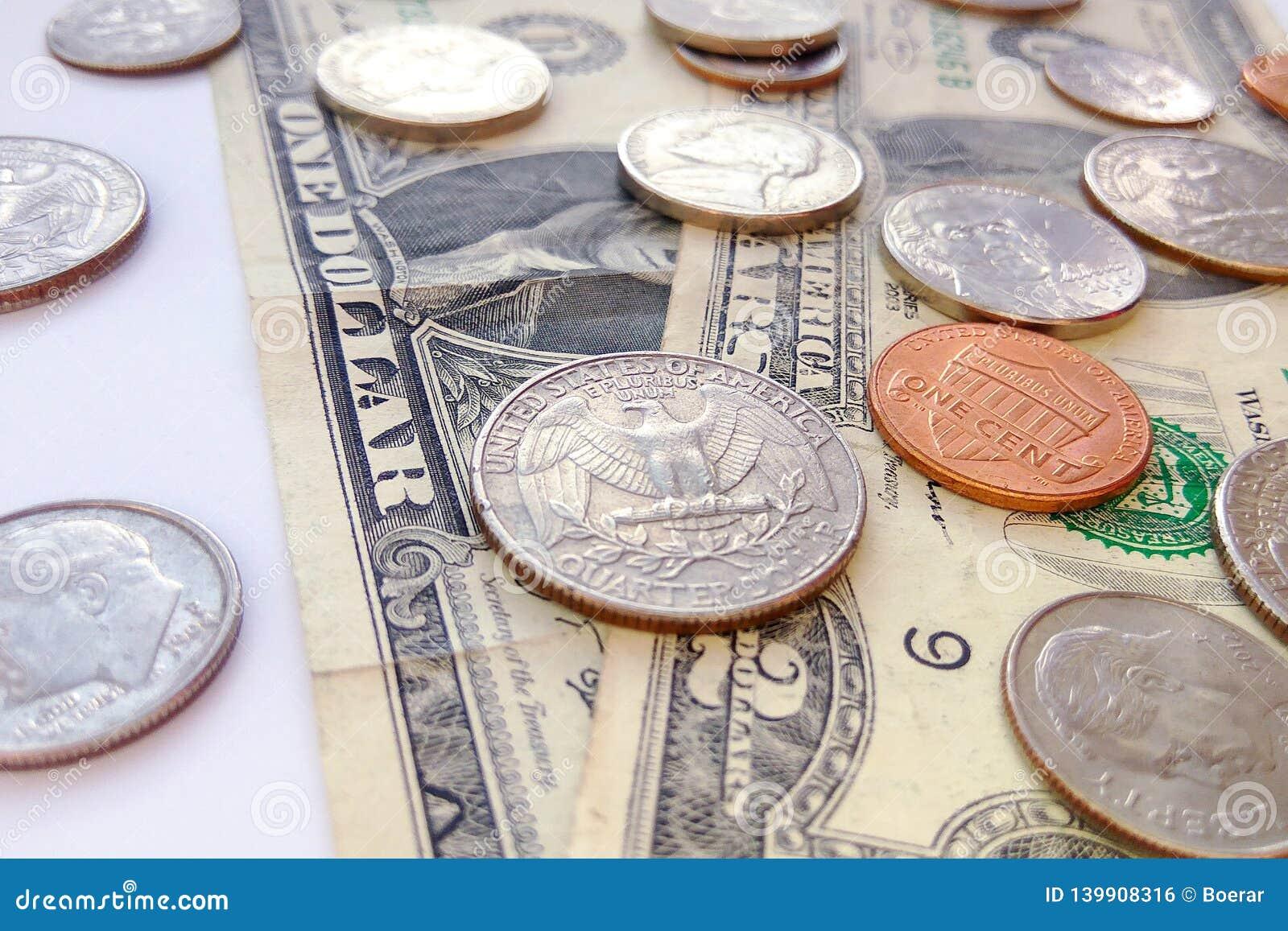 Monete americane del quarto, della moneta da dieci centesimi di dollaro e del penny sul fondo degli S.U.A. dei dollari