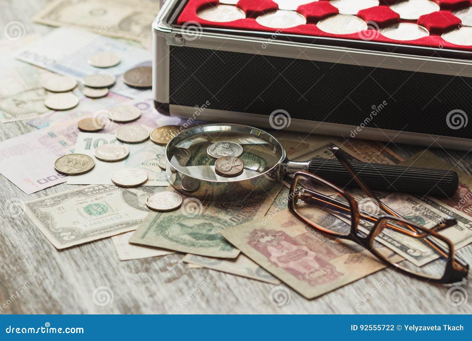 Monete e banconote differenti del ` s del collettore con una lente d ingrandimento
