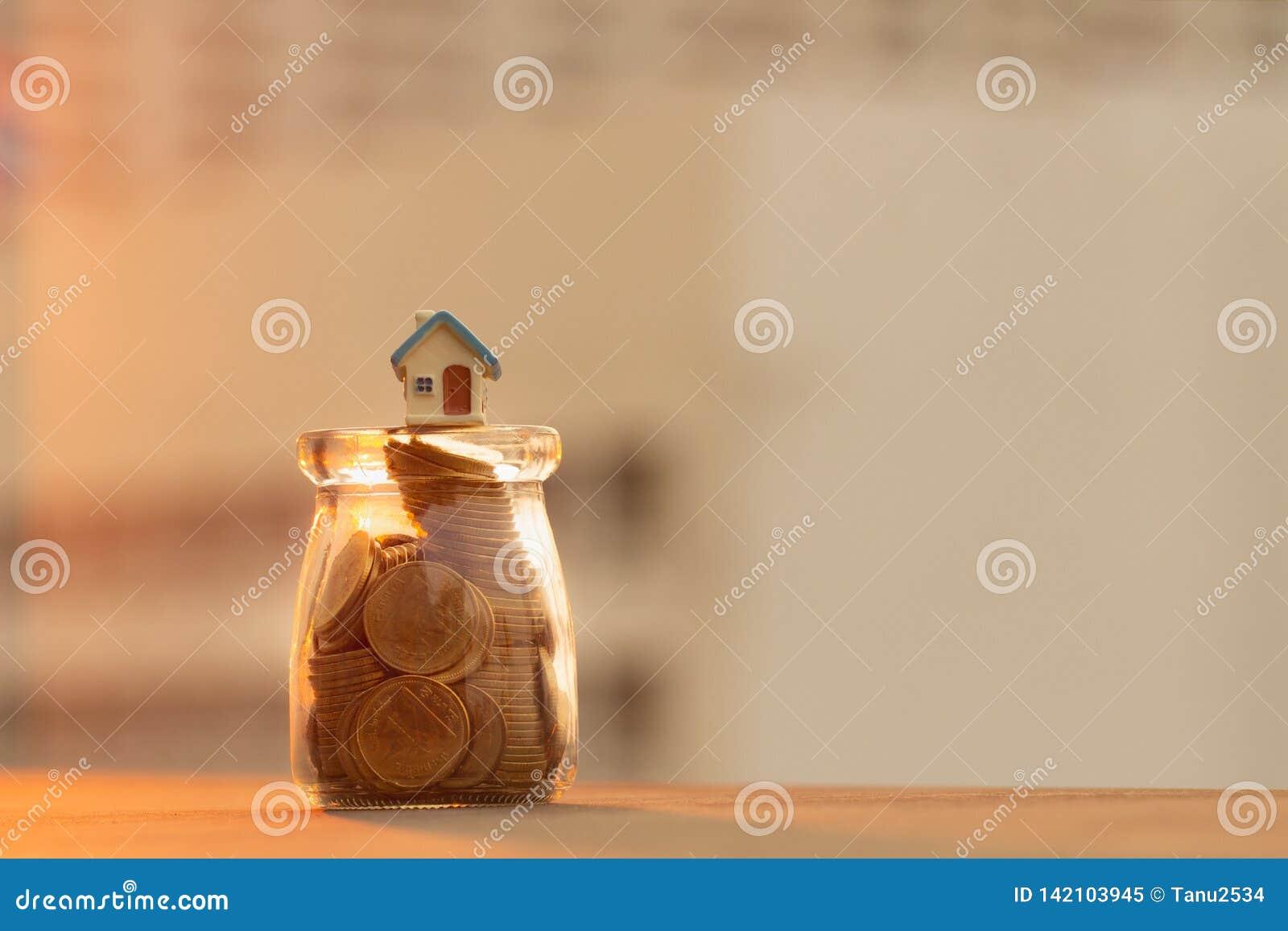 Monety i dom w butelce; pieniądze oszczędzania pojęcie