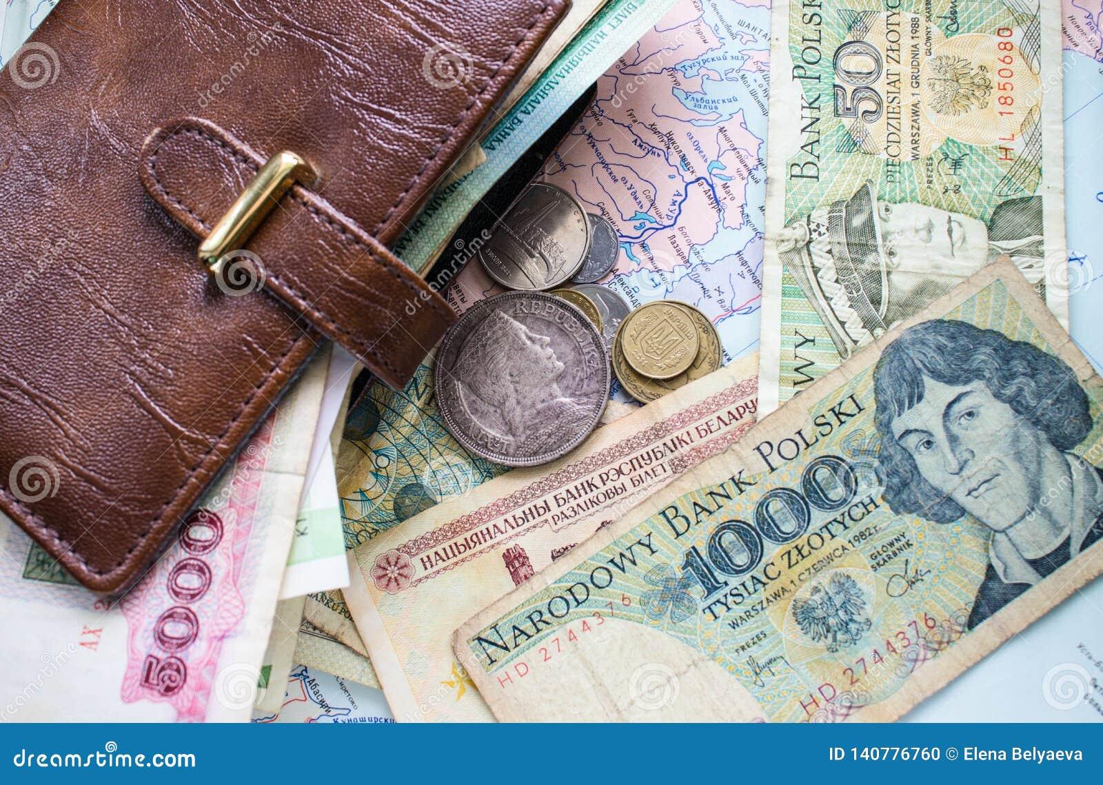 Monety, papierowy pieniądze i rzemienny portfel na tle,