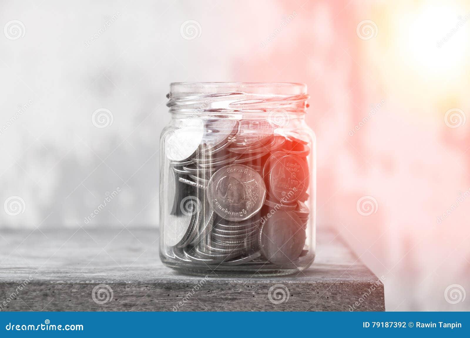Monety w szklanym słoju przeciw, savings monety - inwestyci I interesu pojęcia oszczędzania pieniądze pojęcie