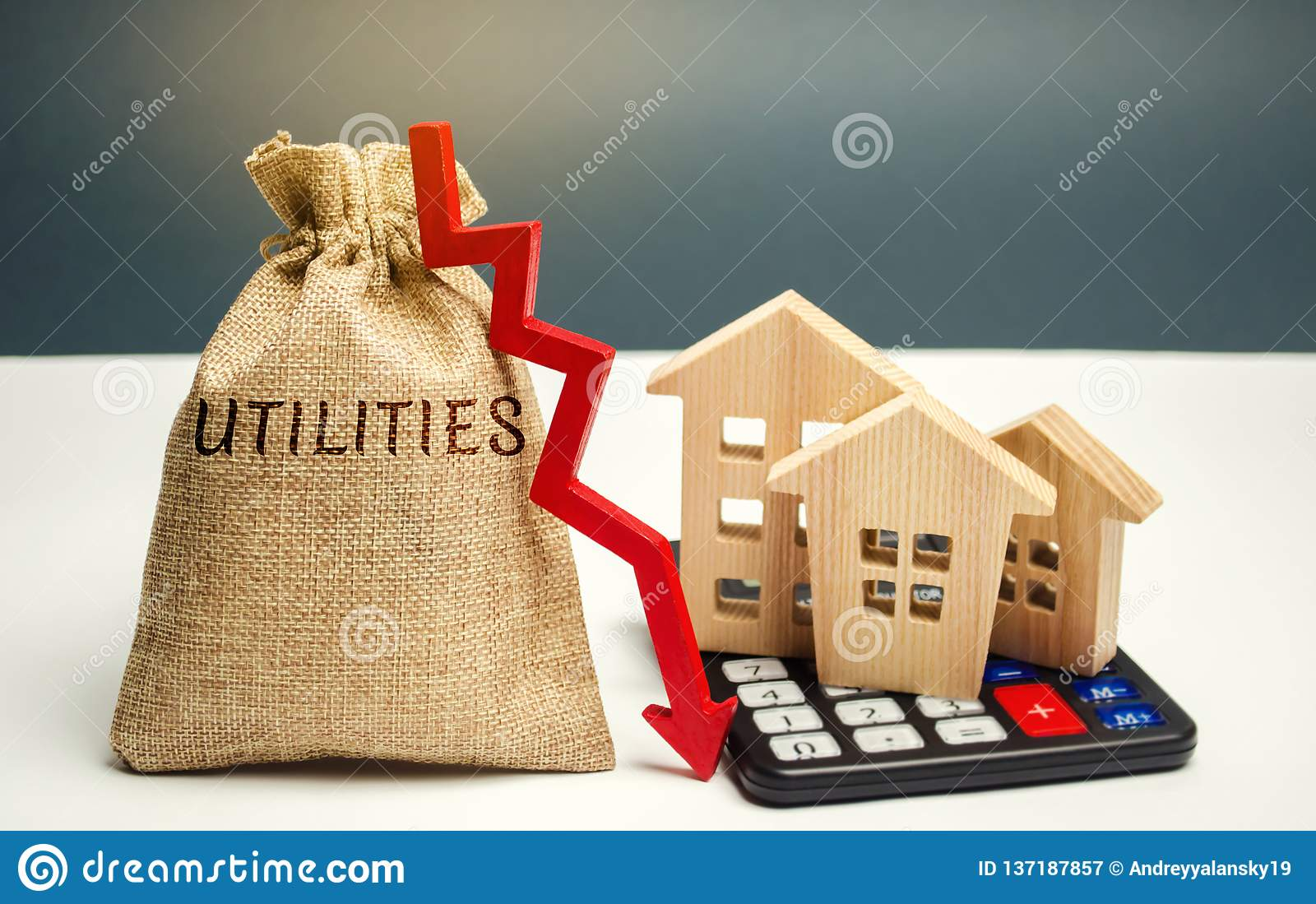 Money bag with the word Utilities and an arrow down and wooden houses on the calculator. Reduced prices for utilities. Low prices
